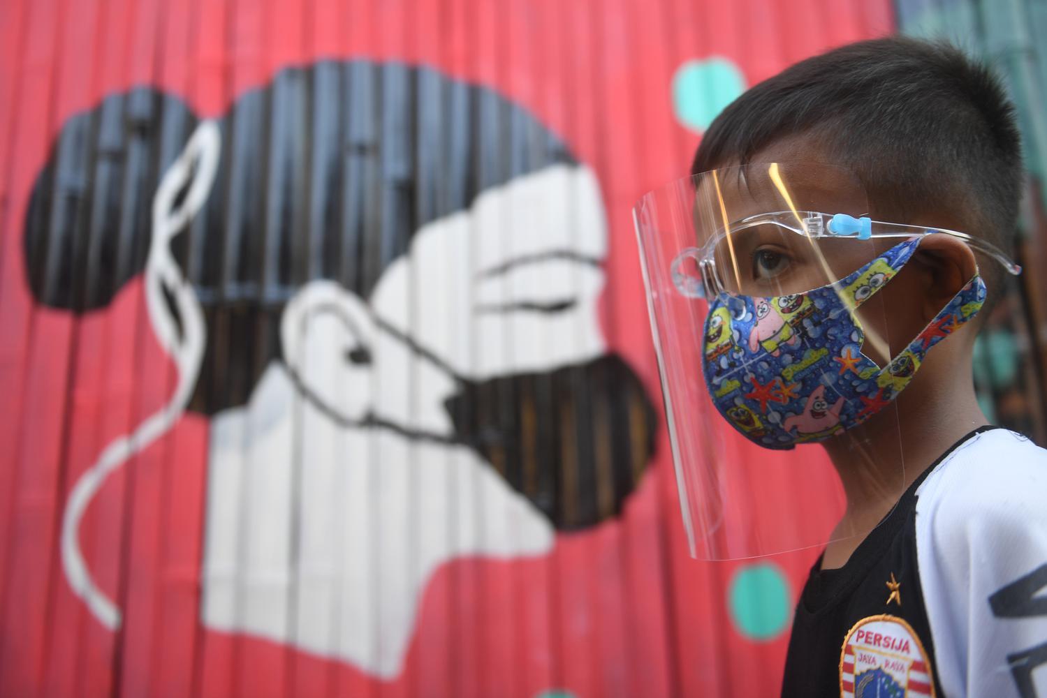 Seorang anak melintasi mural bertema COVID-19 di Jakarta, Senin (27/7/2020). Berdasarkan data dari Satgas Penanganan COVID-19 per 27 Juli 2020, kasus positif COVID-19 di Indonesia telah mencapai 100.303 kasus, dimana 58.173 orang dinyatakan sembuh dan 4.838 orang meninggal dunia.