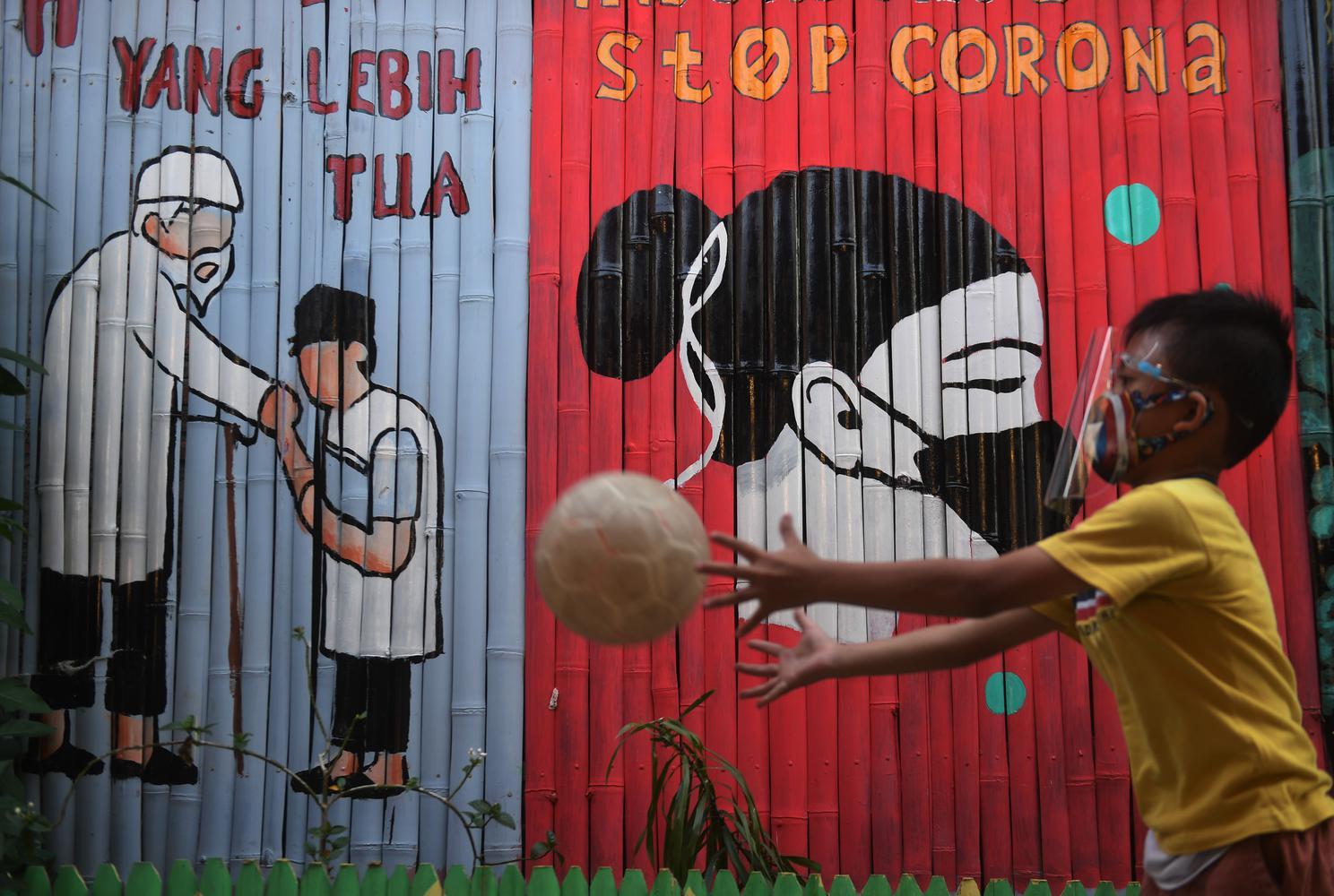 Seorang anak bermain di depan mural bertema COVID-19 di Jakarta, Senin (27/7/2020).