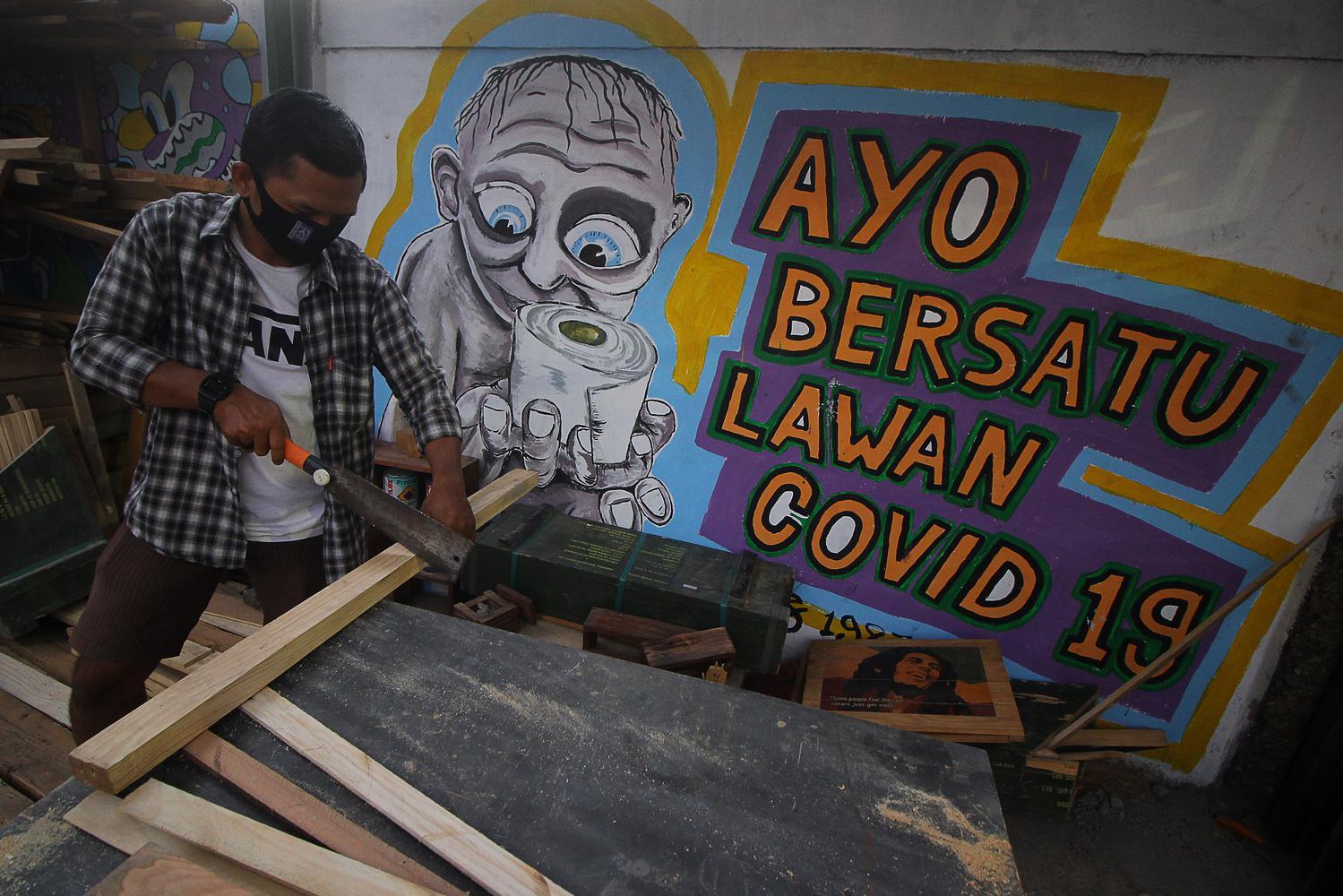 Warga beraktivitas di depan mural tentang COVID-19 di Kampung Jogoloyo, Surabaya, Jawa Timur, Senin (27/7/2020). Berdasarkan data dari Satgas Penanganan COVID-19 per 27 Juli 2020, kasus positif COVID-19 di Indonesia telah mencapai 100.303 kasus, dimana 58.173 orang dinyatakan sembuh dan 4.838 orang meninggal dunia.