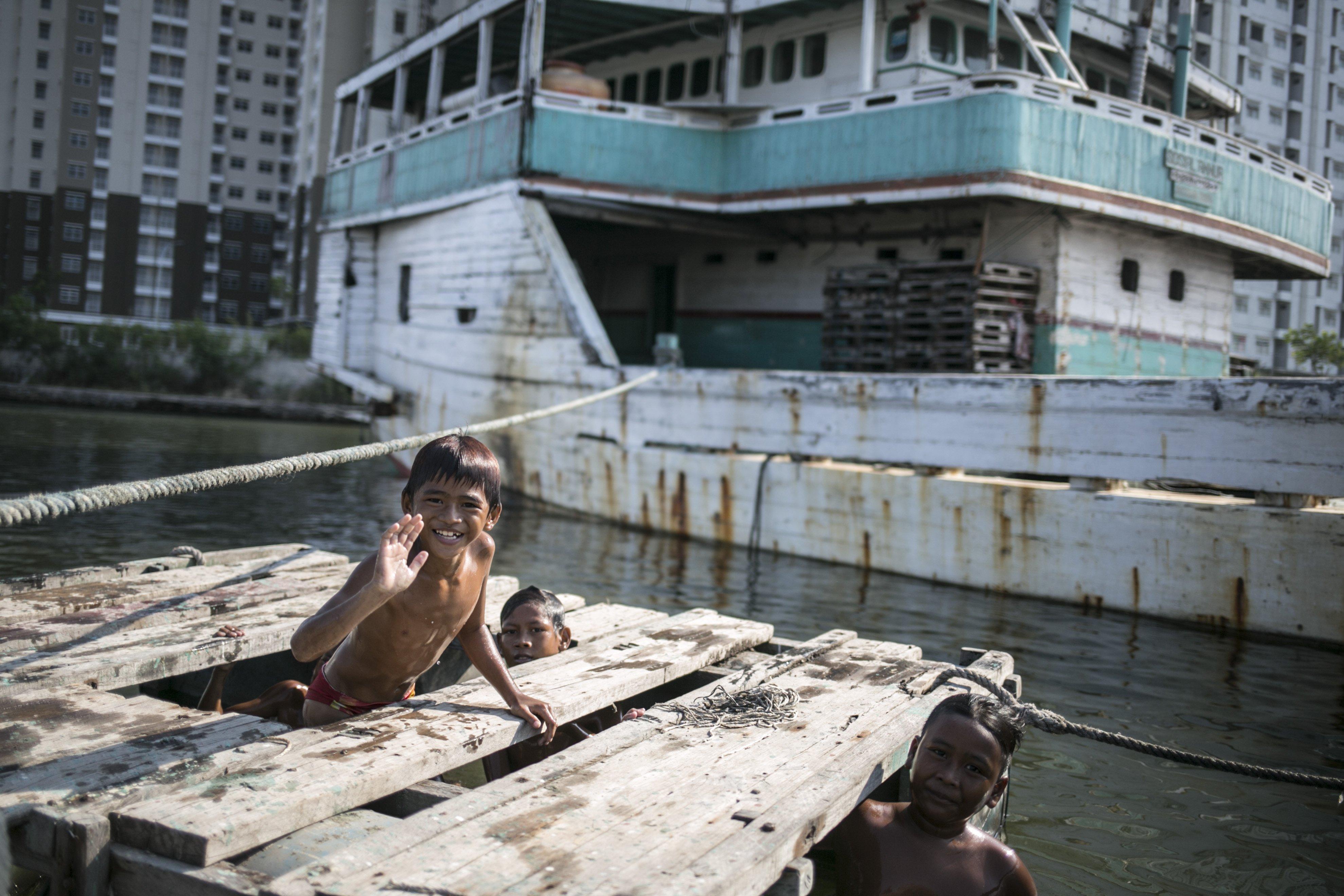 Sejumlah anak berenang di Kawasan Pelabuhan Suda Kelapa, Jakarta Utara, Senin (27/7/2020). Anak-anak ini menjadikan pelabuhan untuk tempat bermain dan mencari rejeki dari para pengunjung yang datang ke pelabuhan.