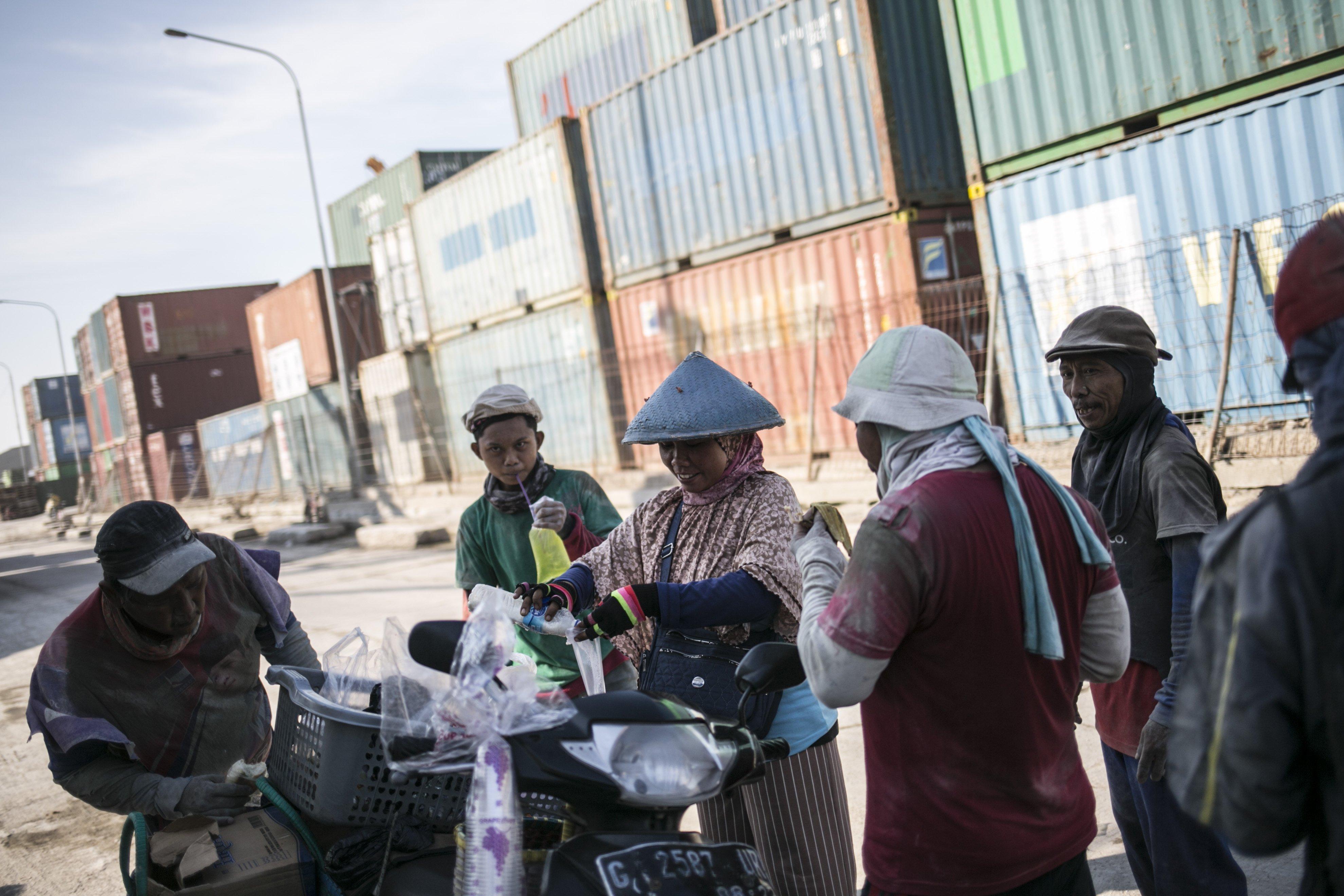 Para pekerja angkut barang membeli minuman dan beristirahat di sela-sela pekerjaan di Pelabuhan Sunda Kelapa, Jakarta Utara, Senin (27/7/2020). Aktivitas di Pelabuhan Sunda Kelapa berangsur normal seperti biasa walaupun di tengah pandemi virus Corona (COVID-19).