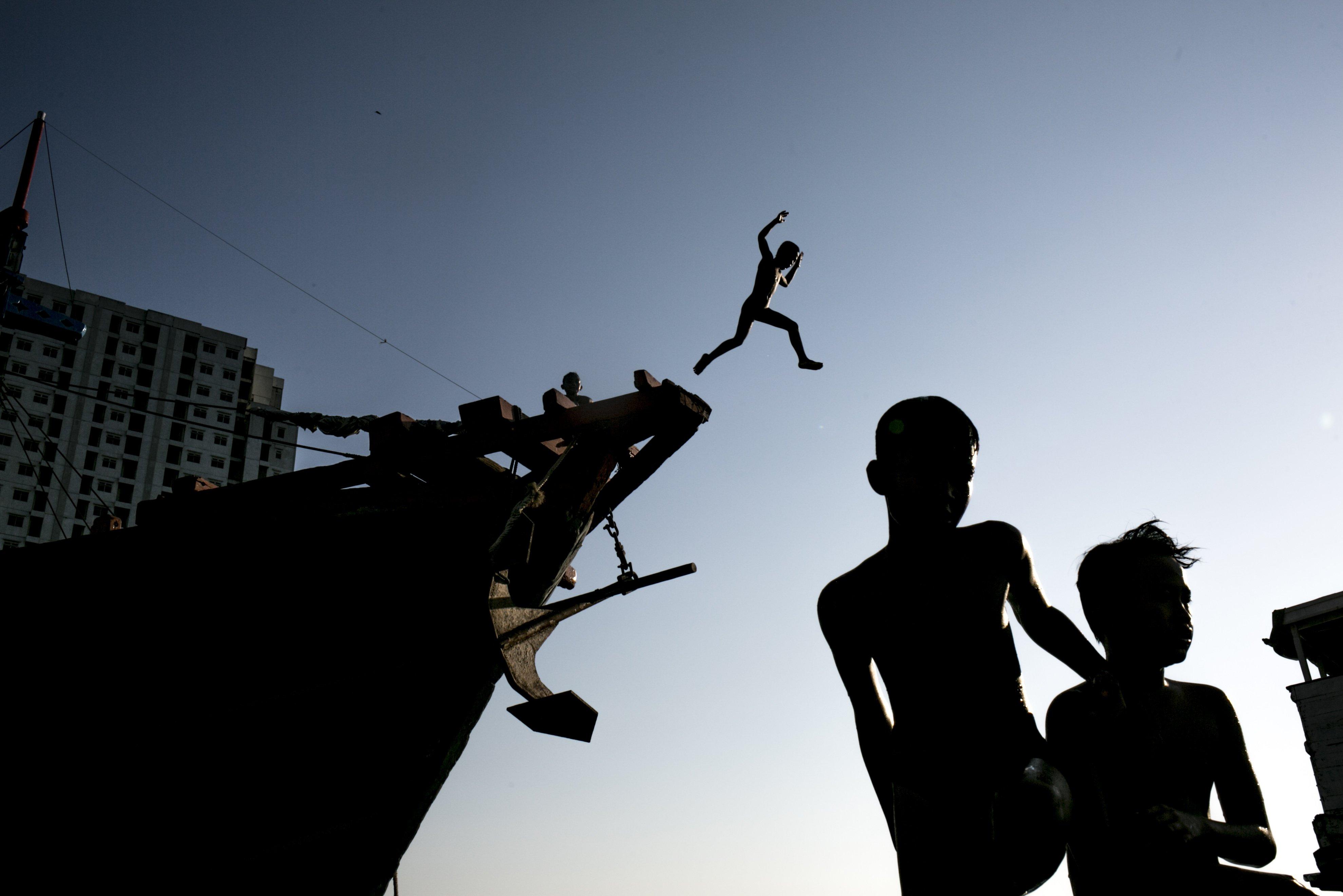Sejumlah anak melompat dari atas kapal di Kawasan Pelabuhan Suda Kelapa, Jakarta Utara, Senin (27/7/2020). Anak-anak ini menjadikan pelabuhan untuk tempat bermain dan mencari rejeki dari para pengunjung yang datang ke pelabuhan.