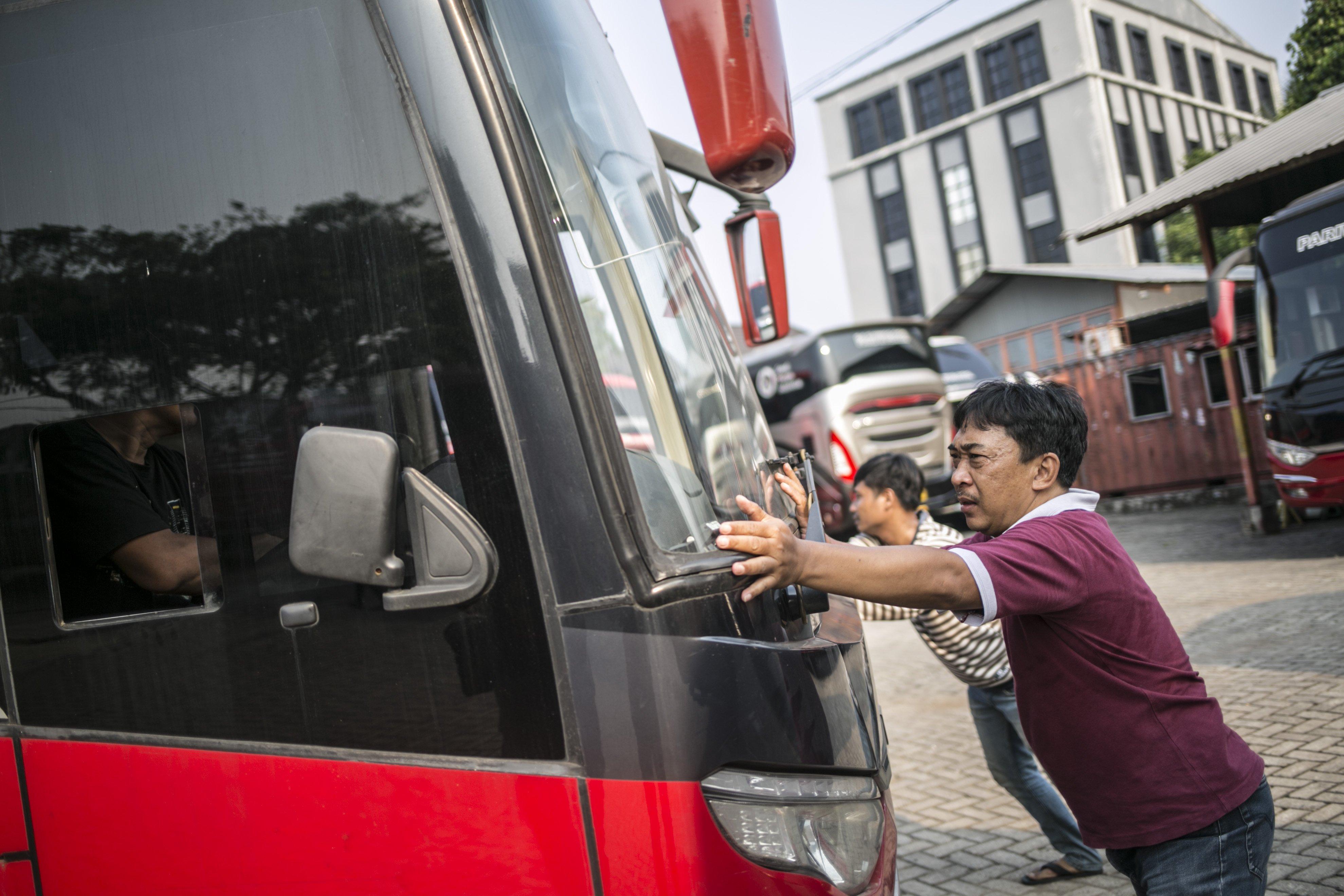Sejumlah mekanik mendorong bus di salah satu pool bus pariwisata di kawasan Tanjung Barat, Jagakarsa, Jakarta, Selasa (28/7/2020). Masih diberlakukannya Pembatasan Sosial Bersekala Besar (PSBB) dan penutupan tempat rekreasi akibat Covid-19, berimbas pada jasa transportasi pariwisata. Sejak bulan Maret pengelola mengaku mengalami penurunan pendapatan dan penyewaan bus hingga 80%.