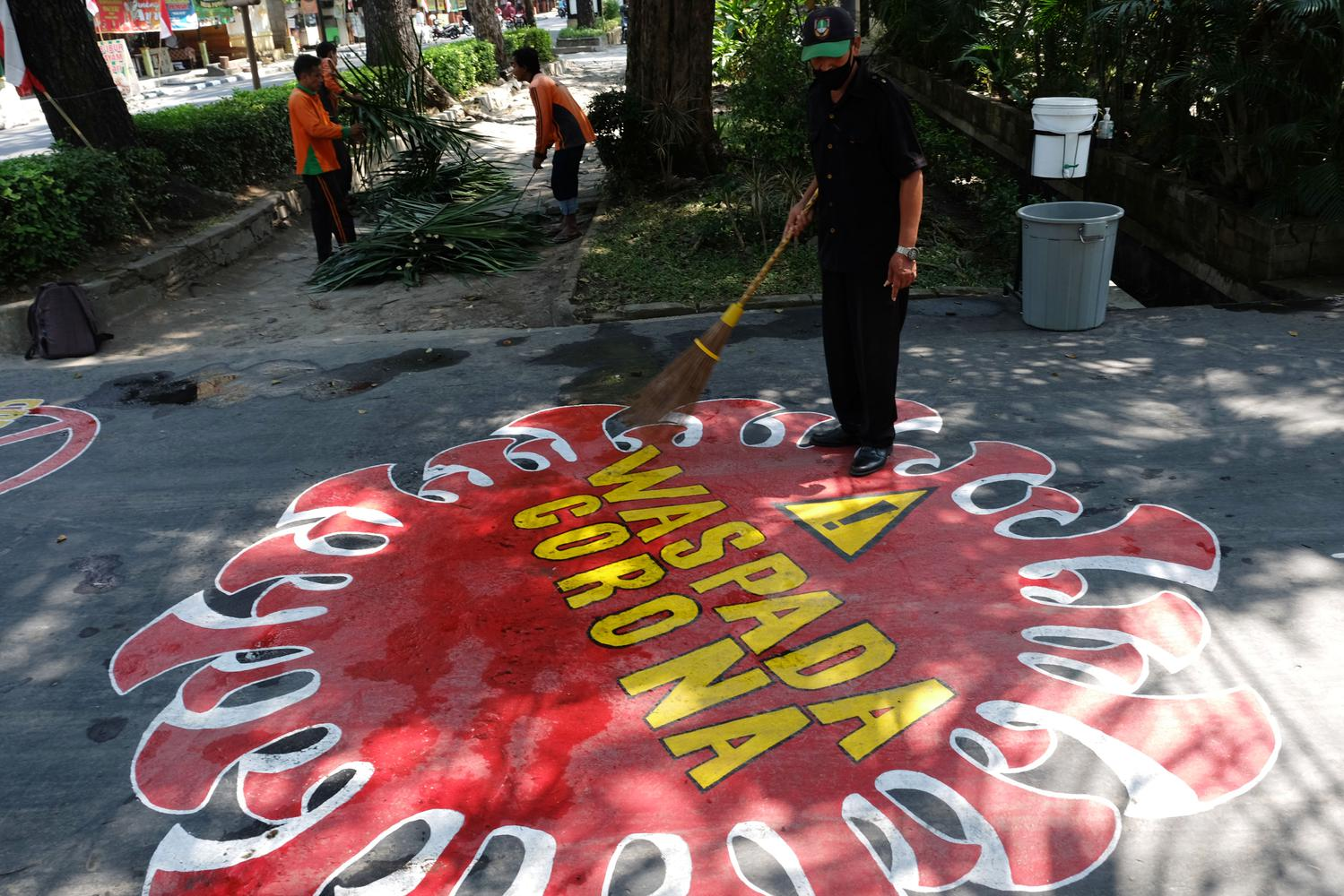 Pekerja membersihkan jalan yang terdapat mural berisi pesan Waspada Penyebaran Virus Corona di halaman Kantor Dinas Lingkungan Hidup, Solo, Jawa Tengah, Senin (3/8/2020). Mural tersebut dibuat agar pengguna jalan mematuhi protokol kesehatan guna mencegah penyebaran COVID-19.