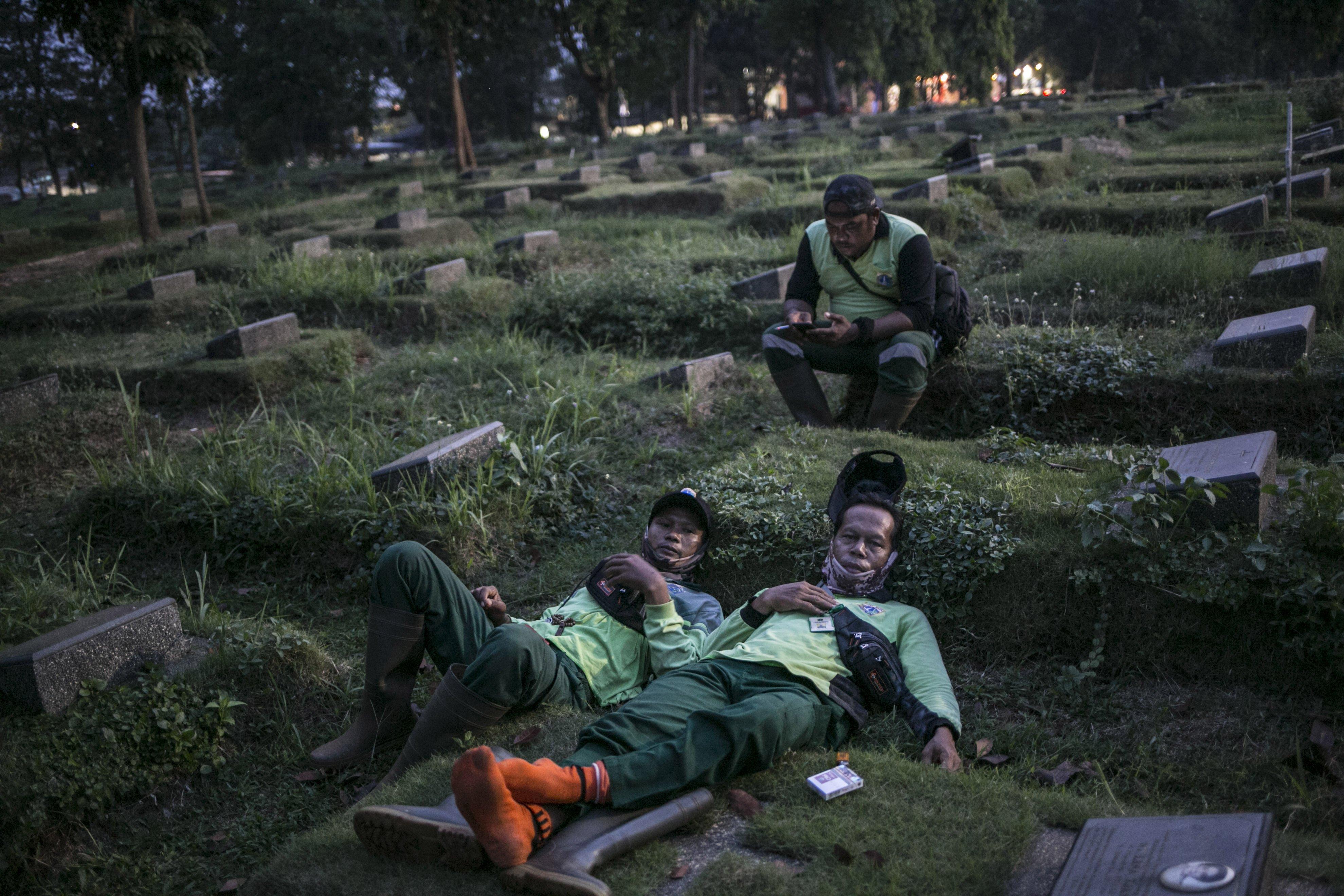 Petugas beristirahat disekitar pusara seusai memakamkan jenazah pasien covid-19 di TPU Pondok Rangon, Jakarta, Kamis (16/7/2020).