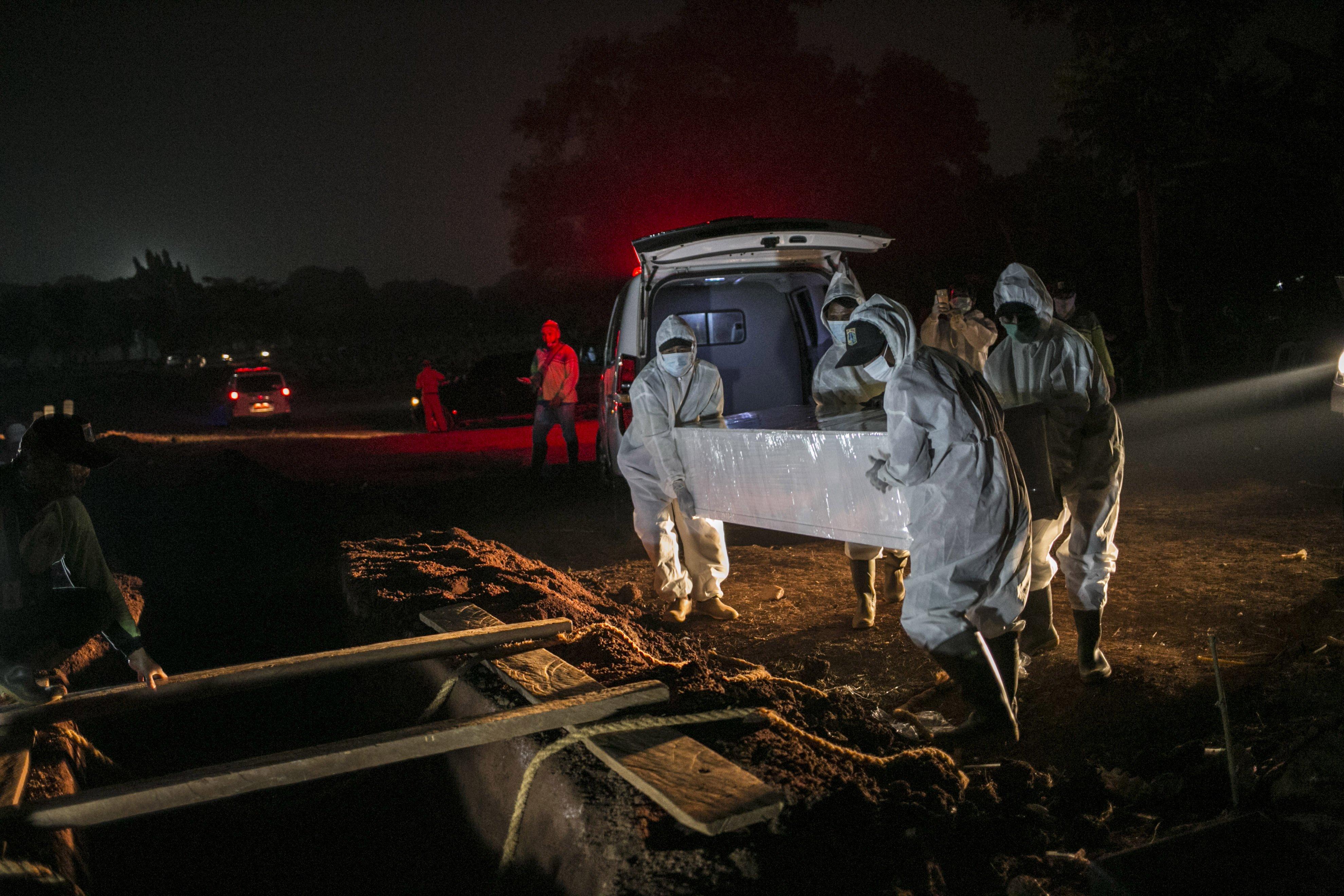 Petugas menggunakan Alat Pelindung Diri (APD) memakamkan jenazah covid-19 di TPU Pondok Rangon, Jakarta, Kamis (16/7/2020).