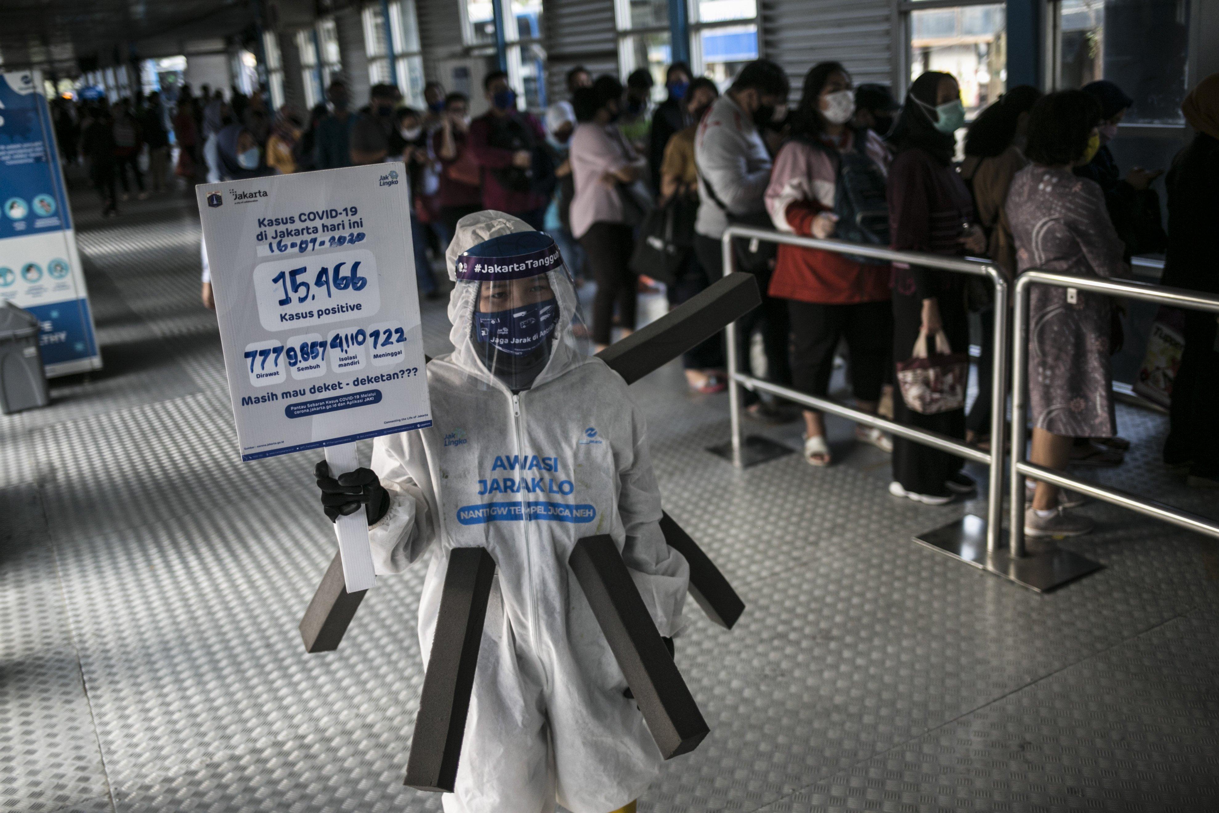 Relawan melakukan sosialisasi untuk mengingatkan penumpang Transjakarta agar selalu menaati protokol kesehatan saat menggunakan transportasi publik guna mengantisipasi penyebaran COVID-19.