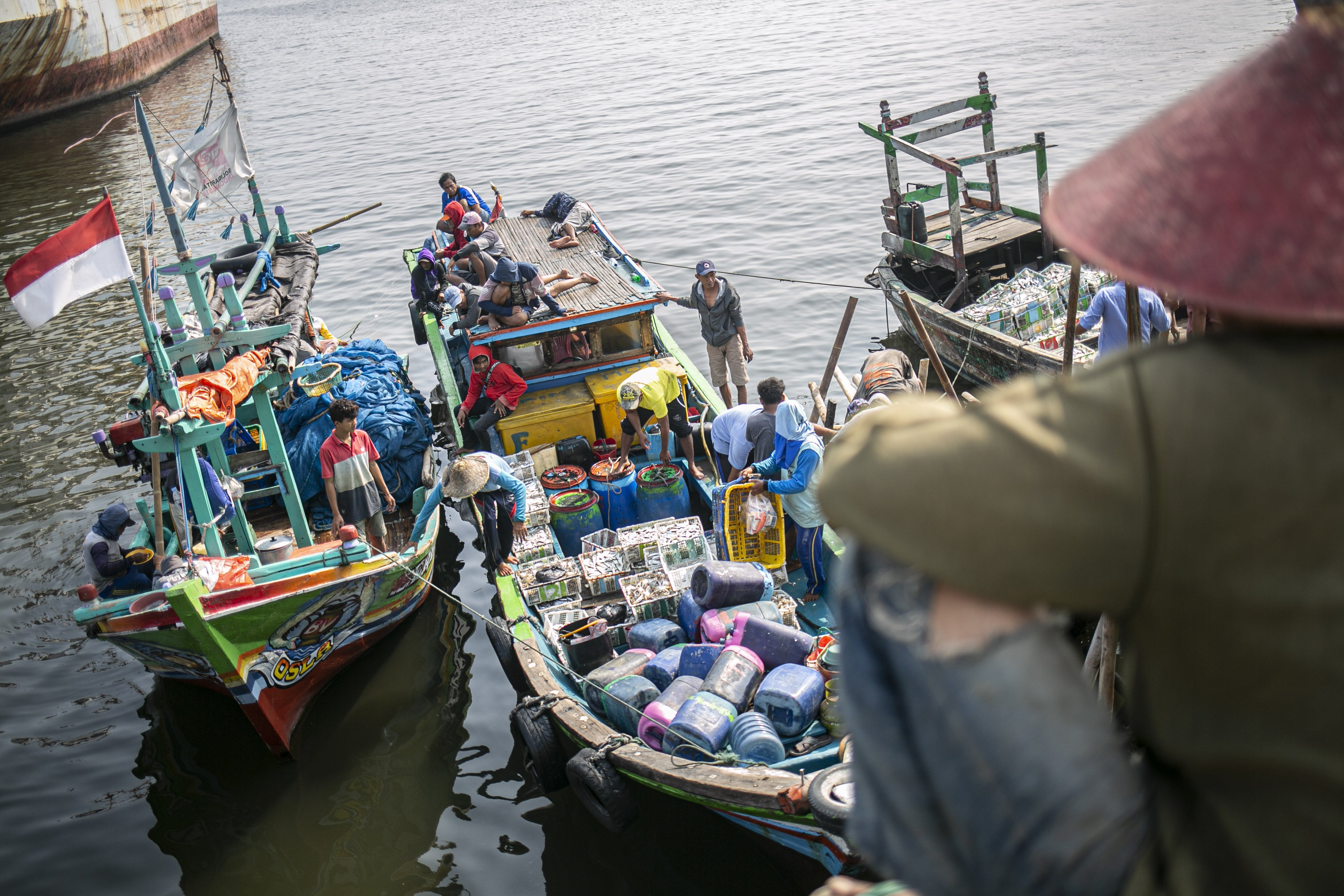 Sejumlah nelayan menurunkan ikan hasil tangkapan di Kampung Nelayan, Jakarta Utara, Minggu (9/8/2020). Kesatuan Nelayan Tradisional Indonesia (KNTI) mengklaim penurunan penjualan tangkapan nelayan mencapai 21 persen dan pendapatan hingga 90 persen akibat merebaknya virus covid-19.