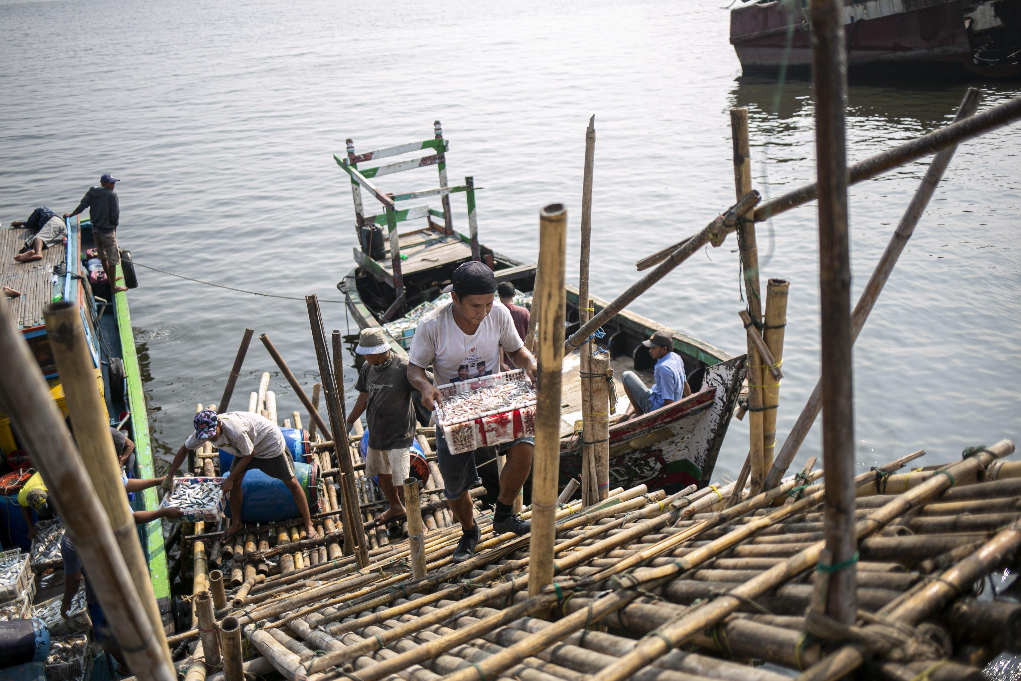 Sejumlah nelayan mengangkat ikan hasil tangkapan di Kampung Nelayan, Jakarta Utara, Minggu (9/8/2020). Kesatuan Nelayan Tradisional Indonesia (KNTI) mengklaim penurunan penjualan tangkapan nelayan mencapai 21 persen dan pendapatan hingga 90 persen akibat merebaknya virus covid-19.