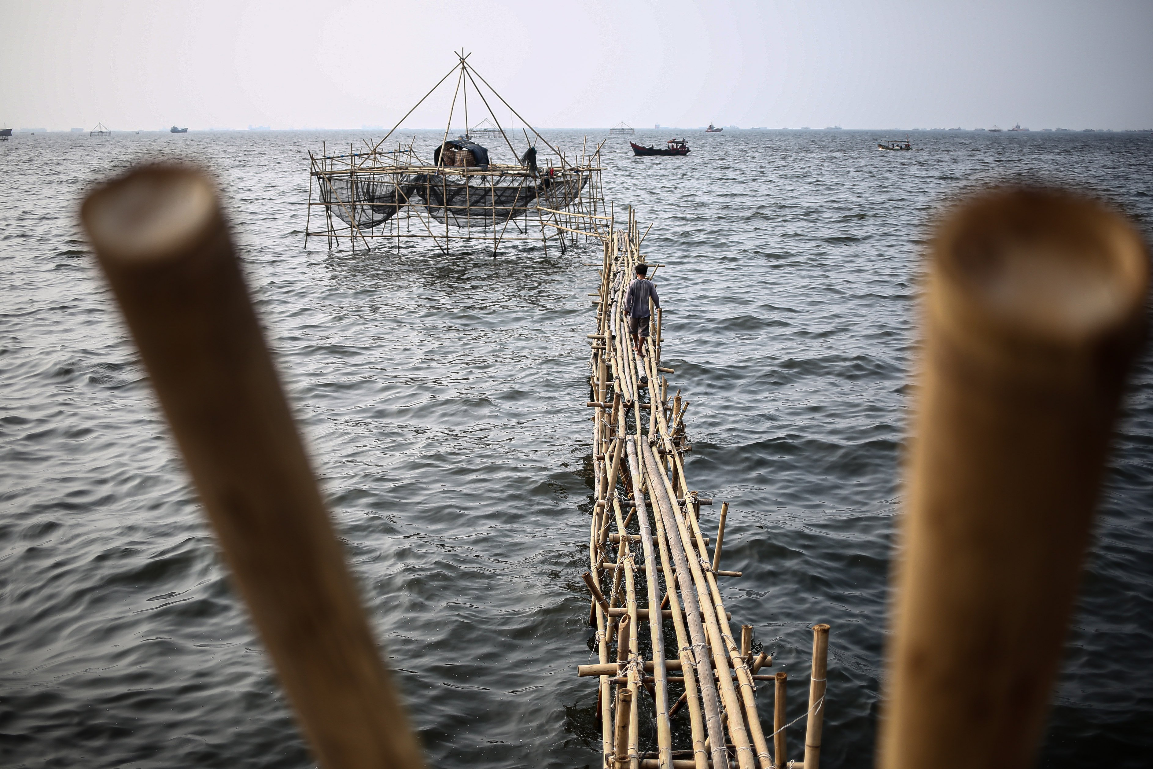 Seorang nelayan berjalan menuju bagan, alat menangkap kerang di Kampung Nelayan, Jakarta Utara, Minggu (9/8/2020). Kesatuan Nelayan Tradisional Indonesia (KNTI) mengklaim penurunan penjualan tangkapan nelayan mencapai 21 persen dan pendapatan hingga 90 persen akibat merebaknya virus covid-19.