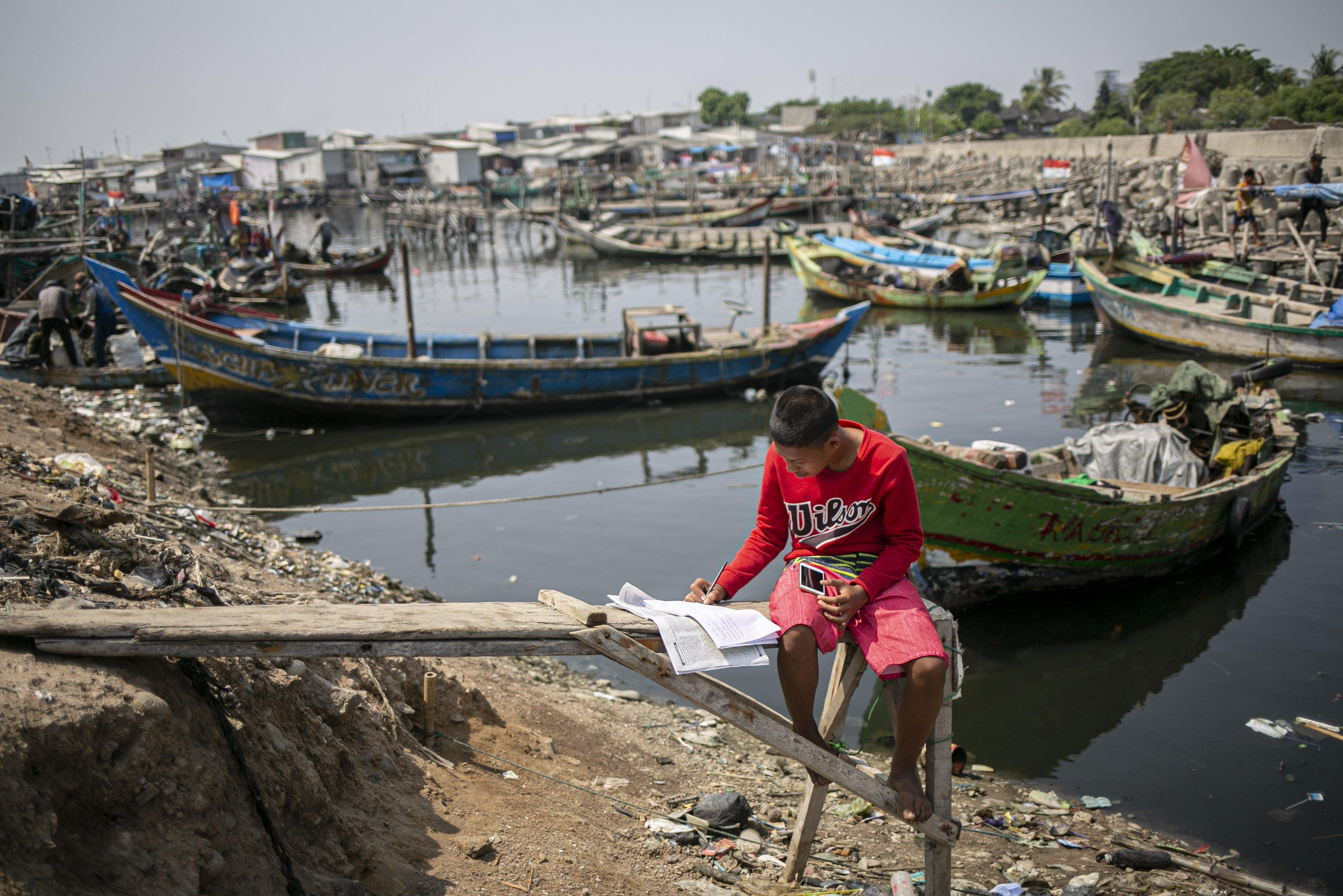 Syihabudin (13) mengikuti proses belajar secara online di pesisir Kampung Nelayan, Jakarta Utara, Minggu (9/8/2020). Kesatuan Nelayan Tradisional Indonesia (KNTI) mengklaim penurunan penjualan tangkapan nelayan mencapai 21 persen dan pendapatan hingga 90 persen akibat merebaknya virus covid-19.