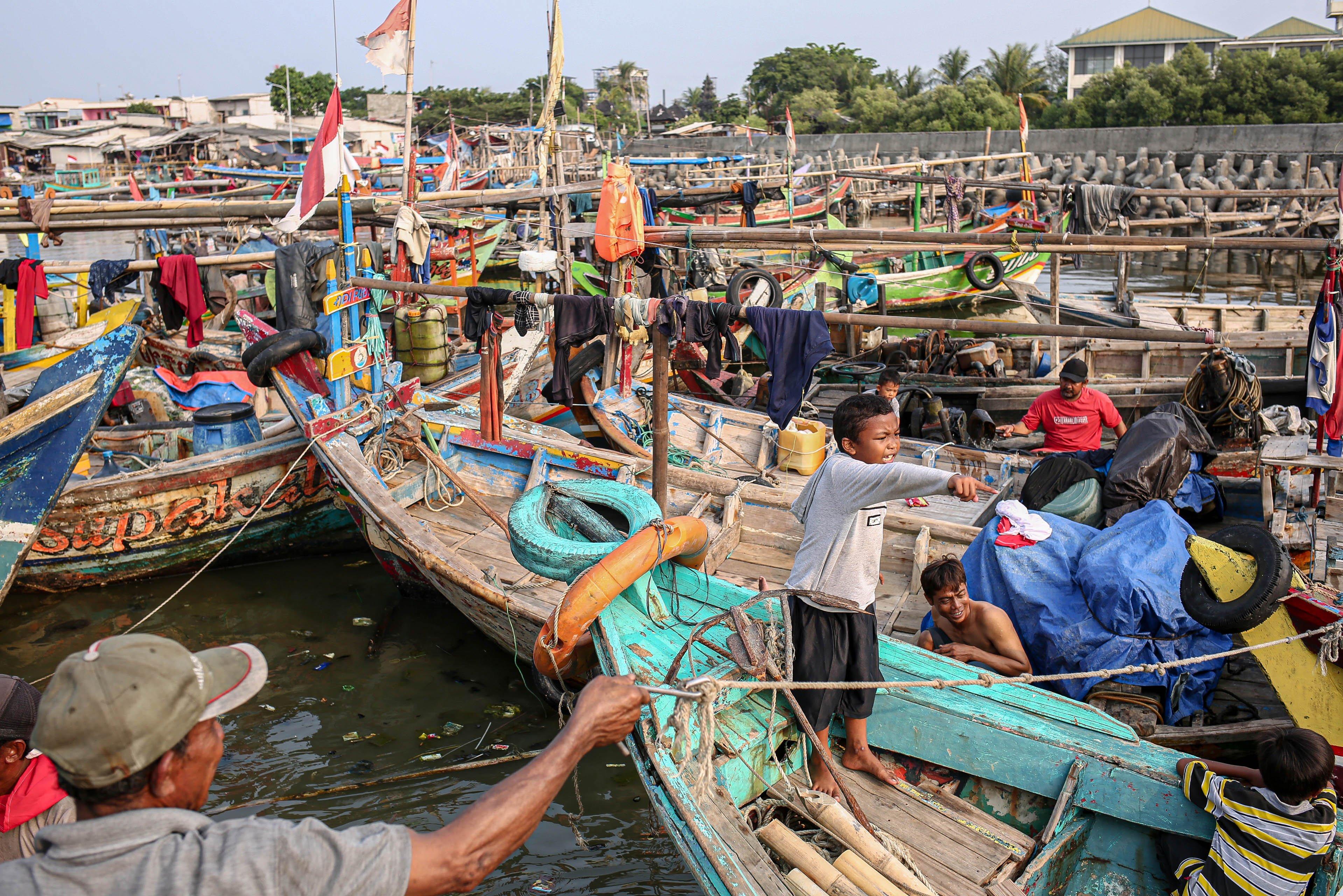 Sejumlah warga menaiki perahu di Kampung Nelayan, Jakarta Utara, Minggu (9/8/2020). Kesatuan Nelayan Tradisional Indonesia (KNTI) mengklaim penurunan penjualan tangkapan nelayan mencapai 21 persen dan pendapatan hingga 90 persen akibat merebaknya virus covid-19.