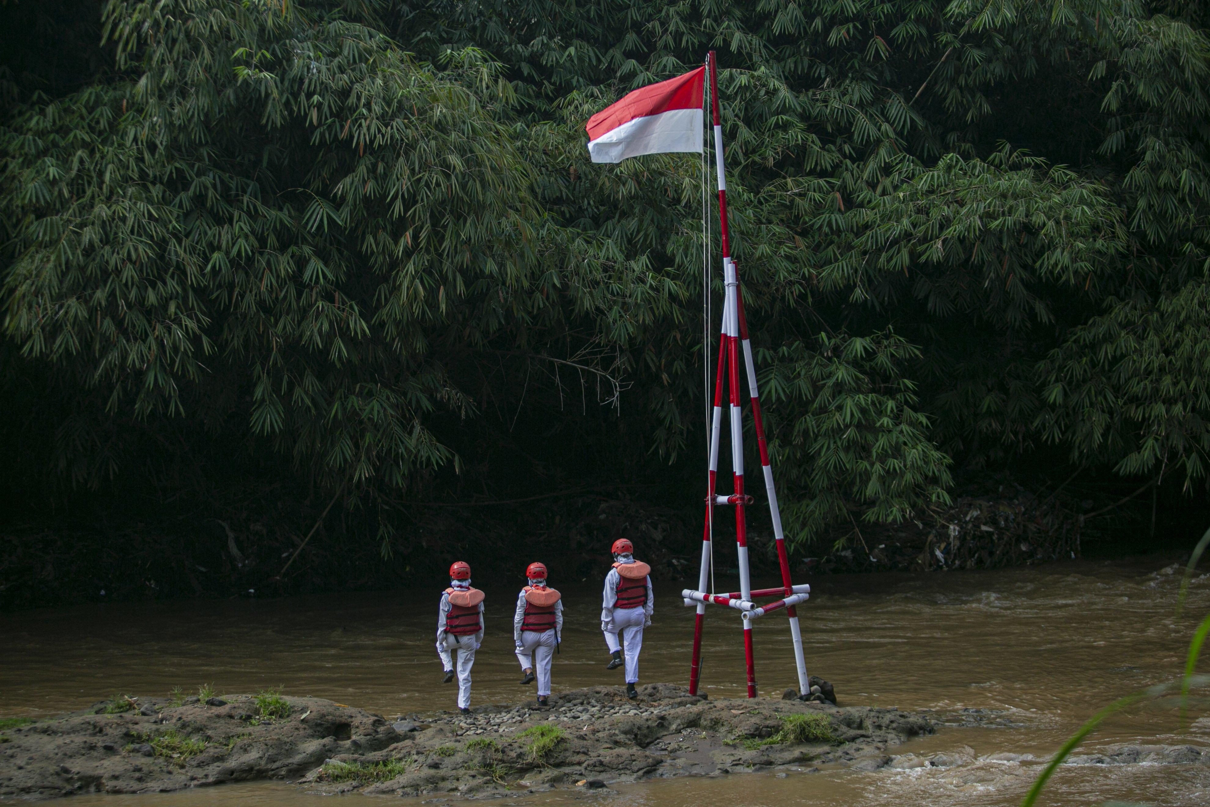 Sejumlah Anggota Komunitas Ciliwung Depok (KCD) melaksanakan rangakai upacara bendera dalam rangka memperingati HUT ke-75 Kemerdekaan Republik Indonesia di Sungai Ciliwung, GDC, Depok, Jawa Barat, Senin (17/8/2020). Pengibaran bendera yang dilakukan di tengah Sungai Ciliwung tersebut merupakan agenda tahunan yang bertujuan agar pemerintah serta masyarakat lebih memperhatikan dan menjaga kondisi Sungai Ciliwung.
