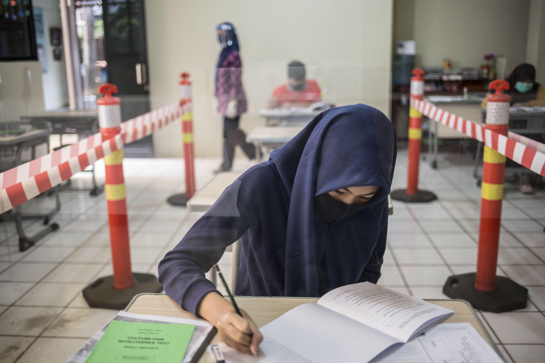 Sejumlah siswa mengikuti proses belajar secara tata muka dengan menggunakan protokol Kesehatan disalah satu sekolah Bekasi, Jawa Barat.