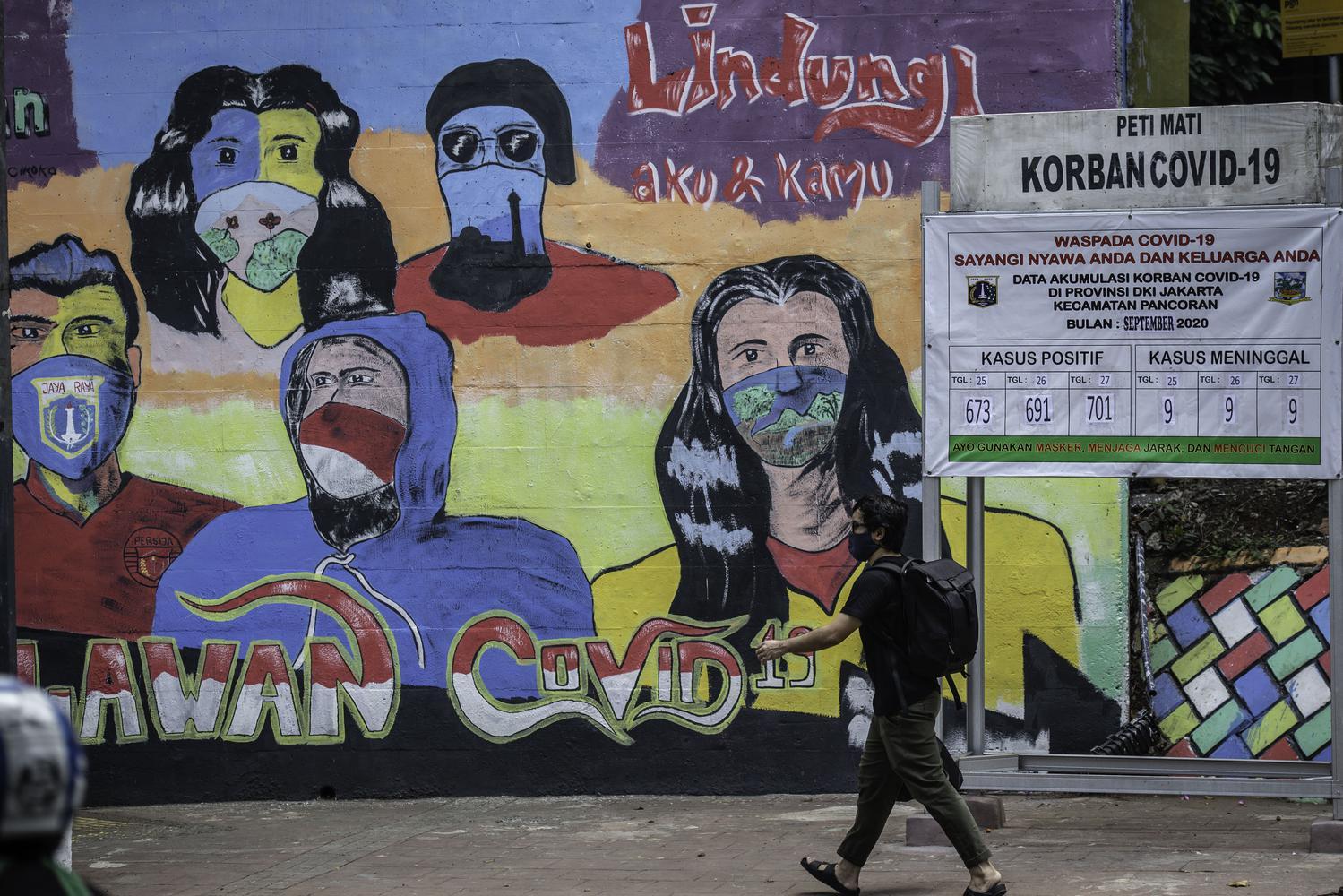 Warga berjalan di dekat mural berisi pesan ajakan menggunakan masker dan replika peti mati COVID-19 di Cikoko, Pancoran, Jakarta, Jumat (2/10/2020). Mural tersebut dibuat untuk mengingatkan masyarakat agar menerapkan protokol kesehatan saat beraktivitas karena masih tingginya angka kasus COVID-19 secara nasional.