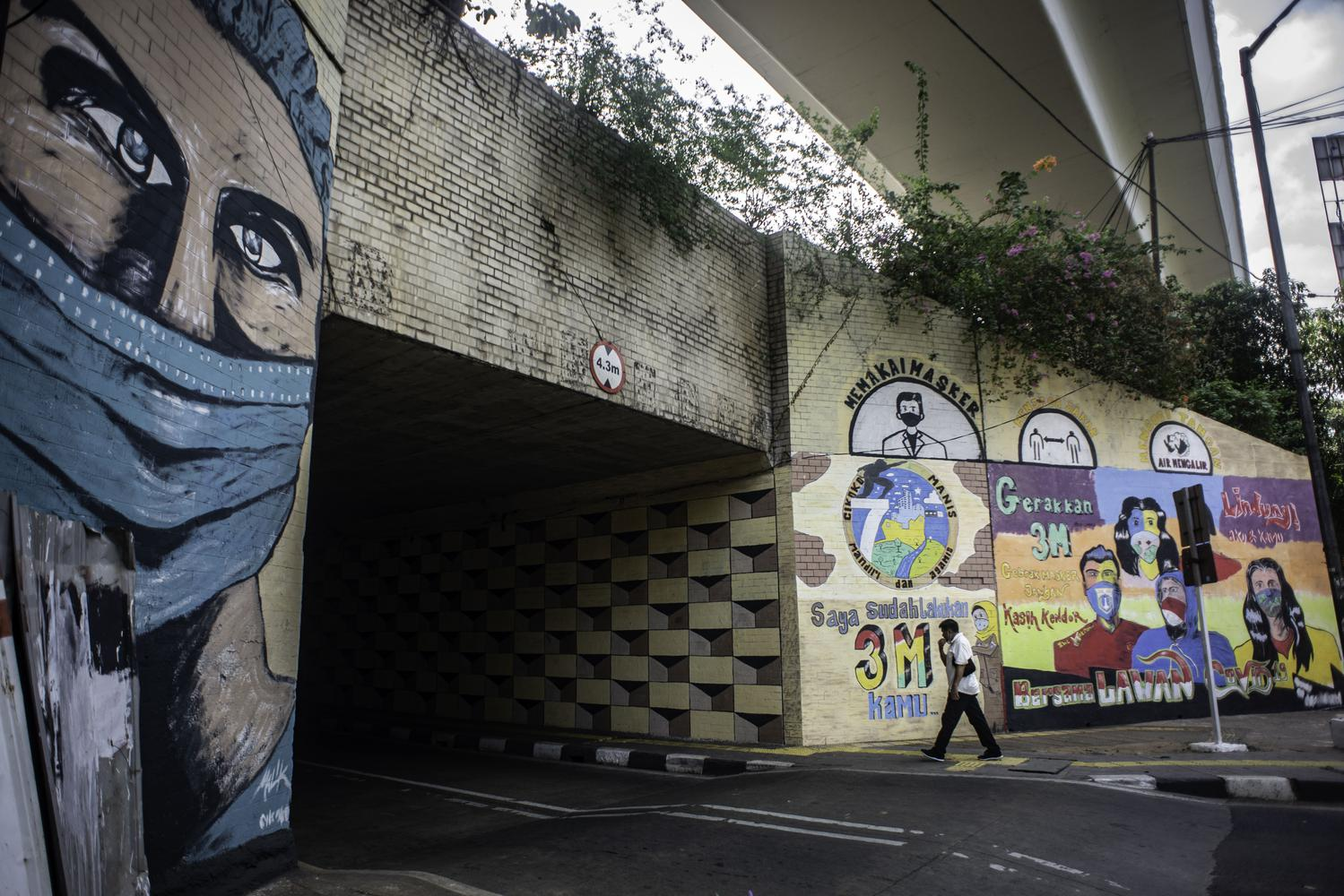 Warga berjalan di dekat mural berisi pesan ajakan menggunakan masker di Cikoko, Pancoran, Jakarta, Jumat (2/10/2020). Mural tersebut dibuat untuk mengingatkan masyarakat agar menerapkan protokol kesehatan saat beraktivitas karena masih tingginya angka kasus COVID-19 secara nasional.