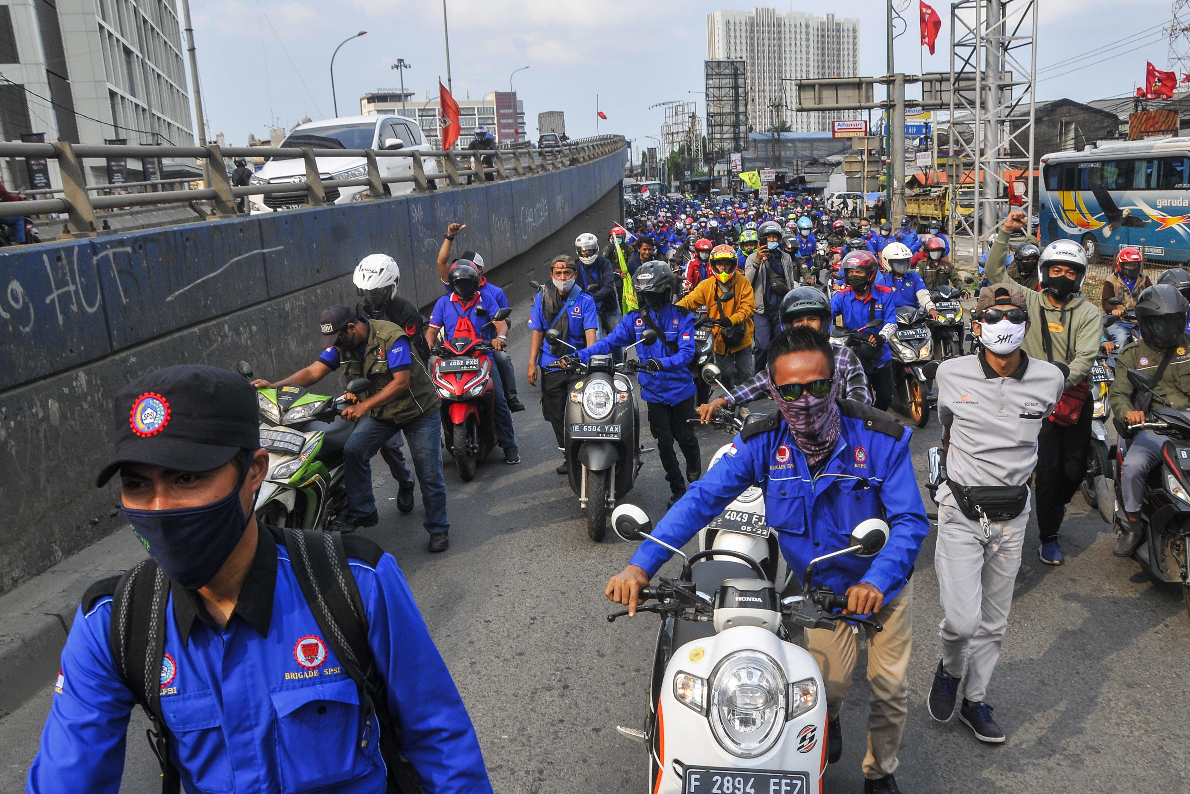 Sejumlah buruh dari berbagai aliansi menggelar aksi dorong motor di Jalan raya Cikarang-Cibarusah, Kabupaten Bekasi, Jawa Barat, Selasa (6/10/2020). Aksi tersebut sebagai kekecewaan buruh atas pengesahan Undang-Undang Cipta Kerja oleh DPR.