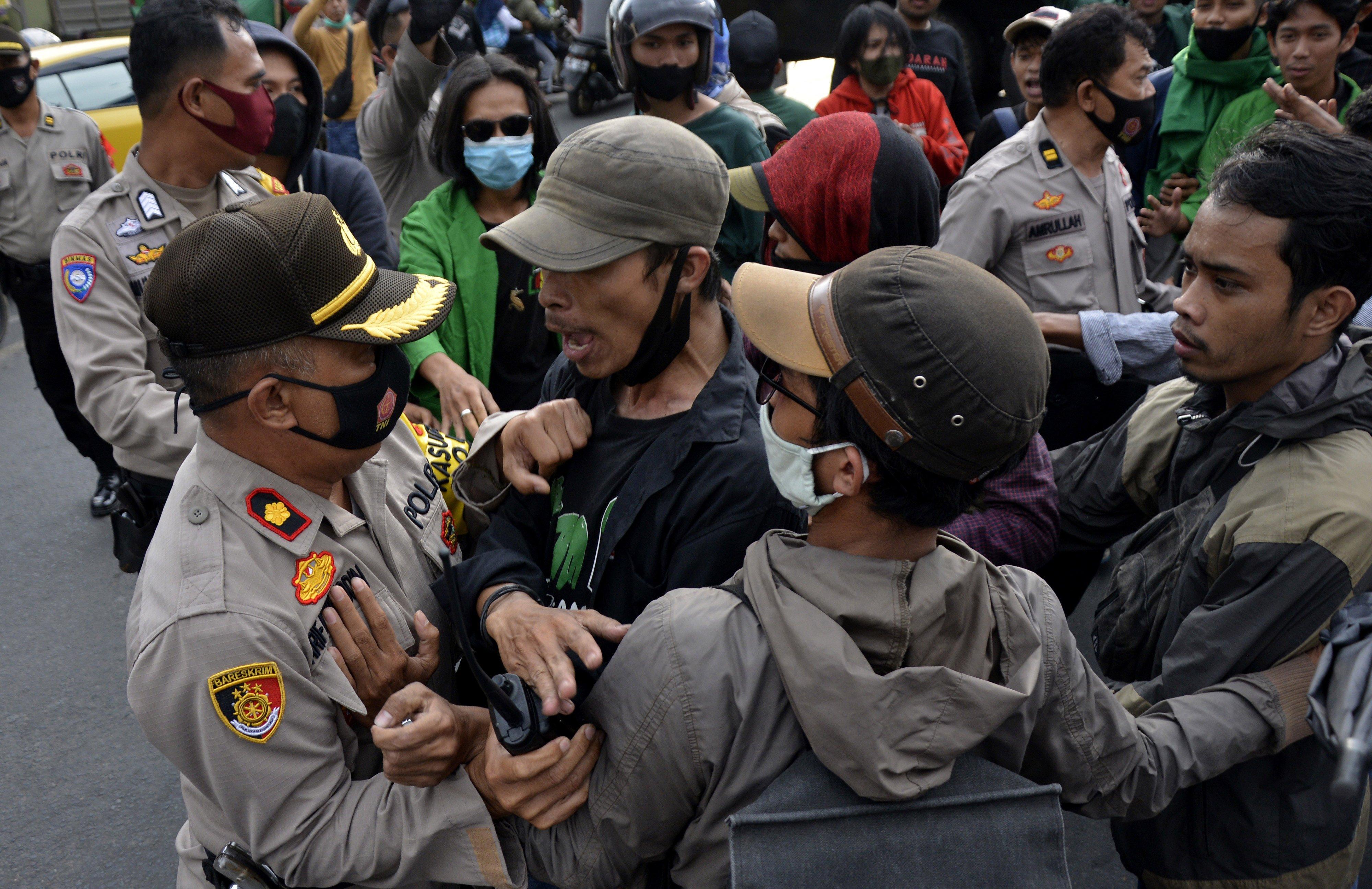 Sejumlah mahasiswa Universitas Islam Negeri (UIN) Makassar terlibat saling dorong dengan aparat kepolisian saat berunjuk rasa, di depan kampus UIN Alauddin, Makassar, Sulawesi Selatan, Selasa (6/10/2020). Dalam aksi unjuk rasa tersebut mereka menolak Undang-undang (UU) Omnibus Law Cipta Kerja yang telah disahkan oleh DPR pada Senin (5/10/2020) karena dinilai merugikan para pekerja dan hanya menguntungkan bagi pengusaha.