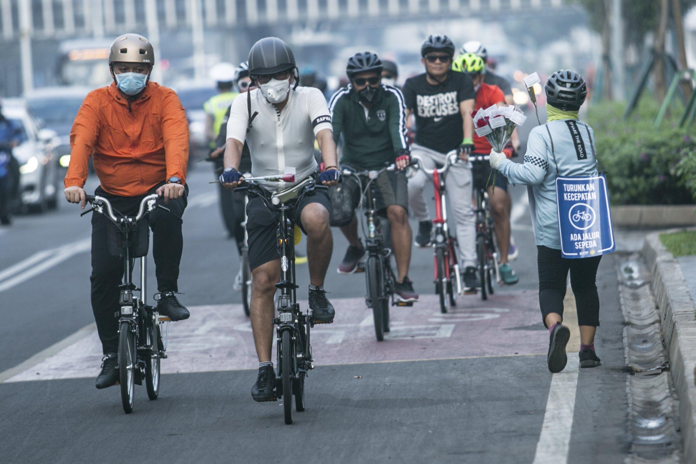 Anggota komunitas sepeda membagikan bunga di Kawasan Jalan Sudirman, Jakarta Pusat. Kegiatan pembagian bunga tersebut bertujuan Untuk mengajak masyarakat menggunakan sepeda agar ramai lingkungan.