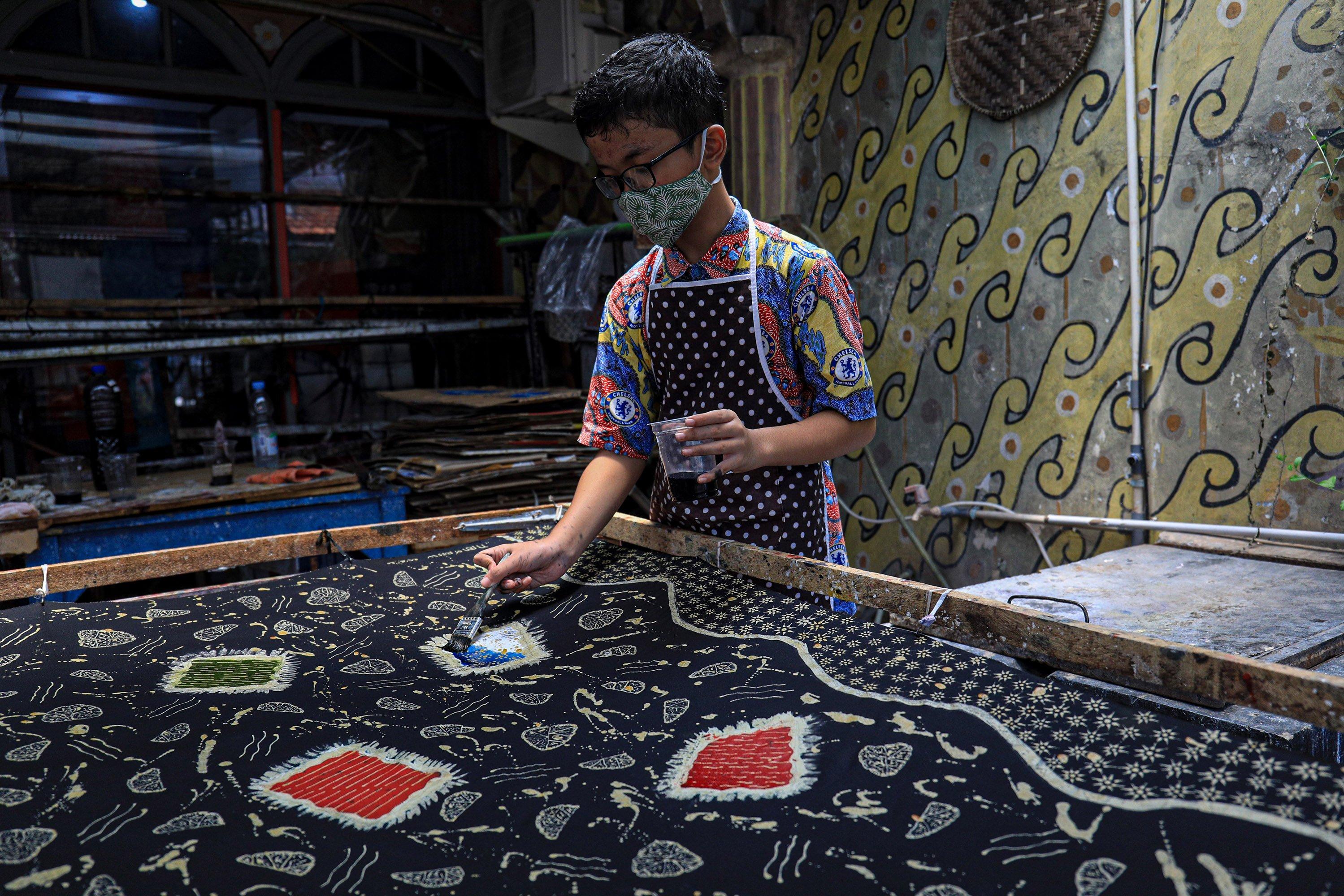 Restu (13), menyelesaikan pembuatan batik di Rumah Batik Palbatu, Jakarta, Rabu (14/10/2020). Rumah Batik Palbatu memberdayakan sejumlah orang berkebutuhan khusus sebagai pengrajin batik, namun menurut pemilik saha, pendapatannya menurun drastisch hingga tak ada pembeli semenjak merebaknya pandemi COVID-19.