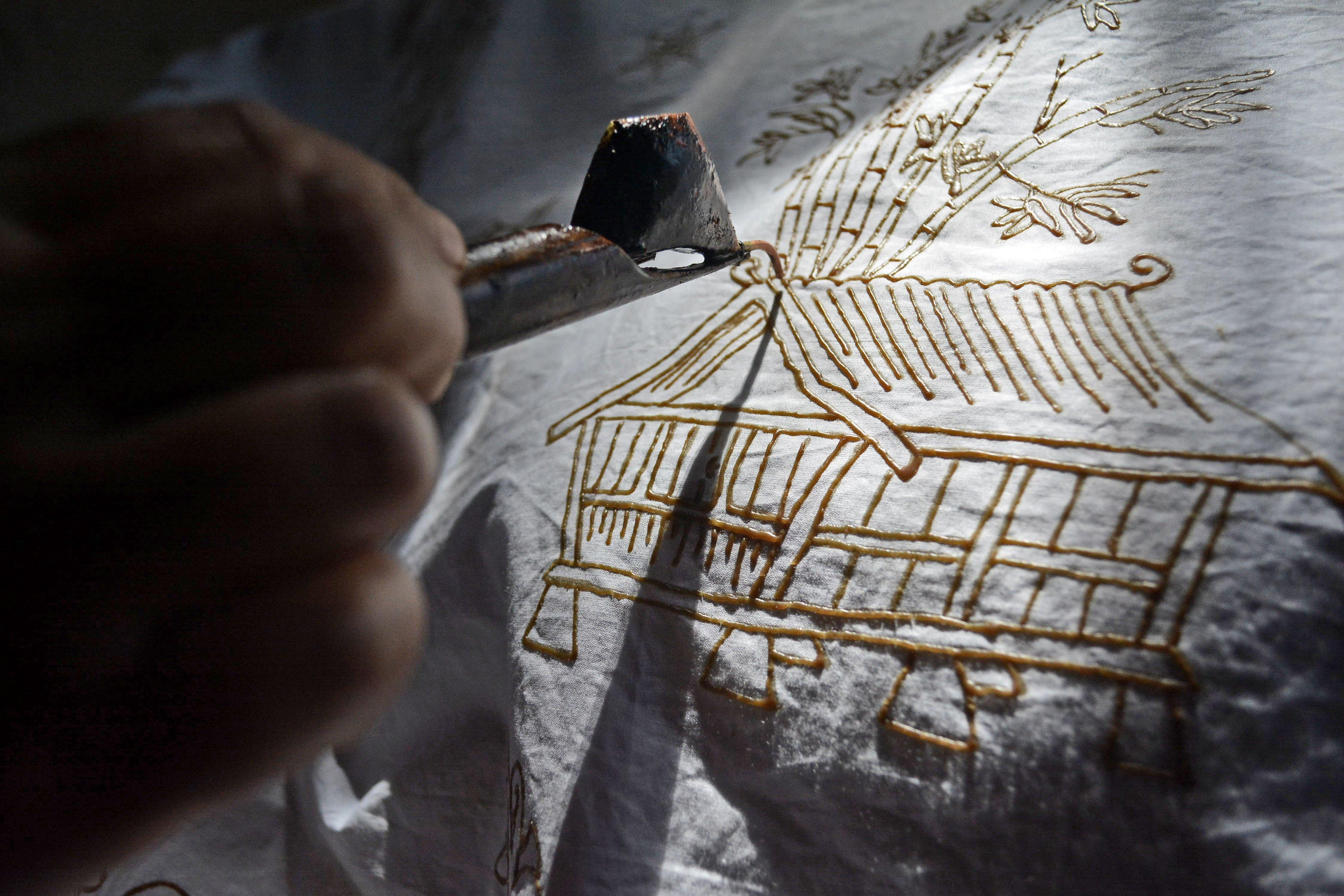 Perajin menyelesaikan pembuatan batik tulis pasiran motif Leuit Pare di Samarang, Kabupaten Garut, Jawa Barat, Kamis (15/10/2020). Perajin kelompok batik Nirmala tersebut mempunyai ciri khas motif batik tulis seperti Leuit Pare, Mayang Kahuripan, Sampeu Antanan, dan Kembang Katresna yang dijual Rp.1 juta hingga Rp.1,5 juta tergantung tingkat kesulitan. ANTARA FOTO/Candra Yanuarsyah/agr/hp.