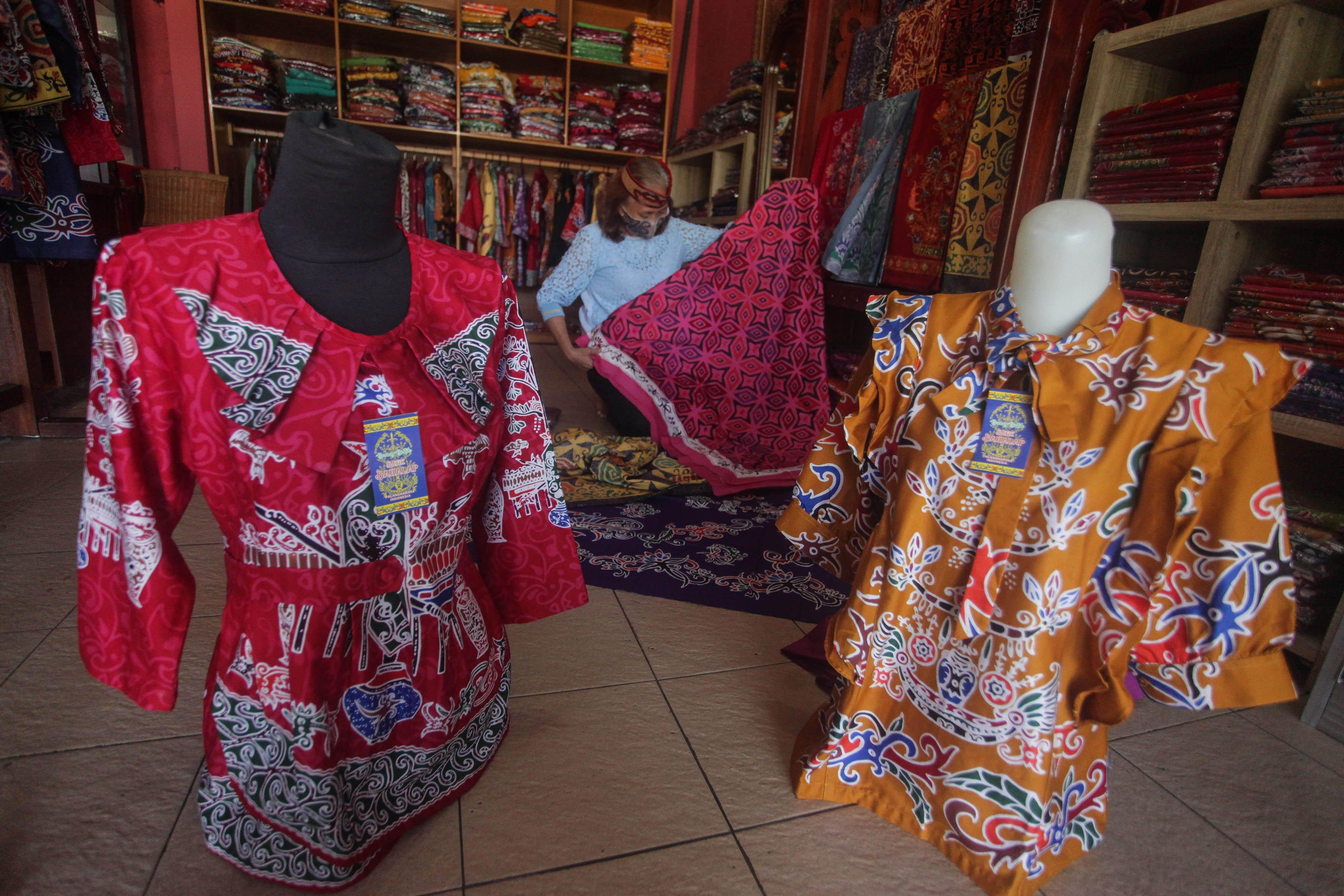 Perajin Batik Bahalap merapikan kain batik tulis motif khas Kalteng yang dijual di kiosnya, di Jalan Thamrin, Palangkaraya, Kalimantan Tengah, Senin (5/10/2020). Menurut perajin setelah penjualan terpuruk hingga 90 persen karena pandemi COVID-19, kini mulai berangsur pulih kembali dengan menerima berbagai pesanan dari instansi pemerintahan dan pasar online dengan harga jual Rp350 ribu hingga Rp1 juta tergantung jenis motif dan ukuran. ANTARA FOTO/Makna Zaezar/pras.