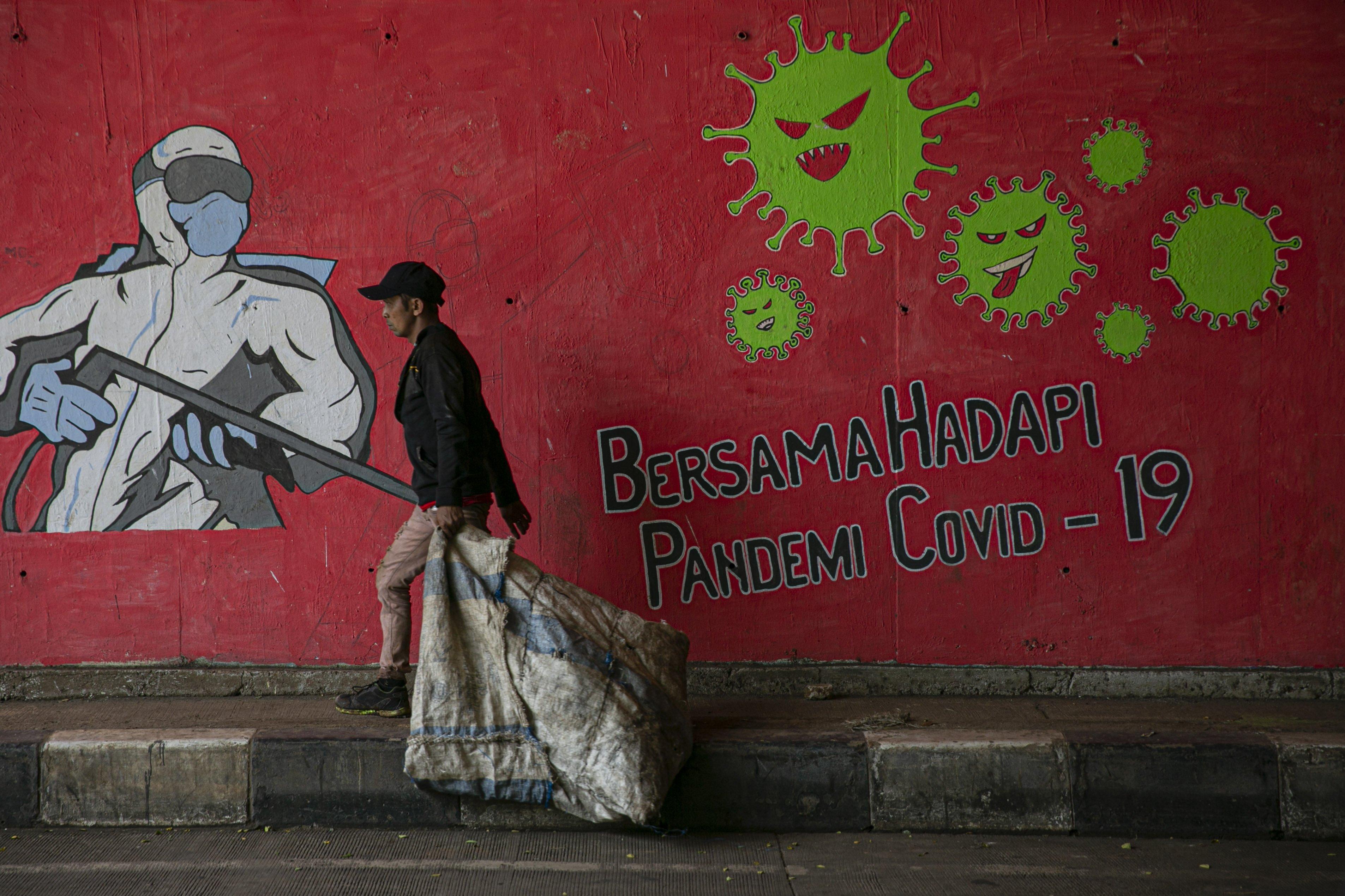 Warga melintas di depan mural tentang pandemi COVID-19 di kawasan Cipayung, Jakarta, Senin (19/10/2020). Indonesia menempati peringkat pertama kasus terbanyak dan angka kematian akibat COVID-19 di Asia Tenggara dengan total 361.867 kasus konfirmasi dan meninggal sebanyak 12.511.