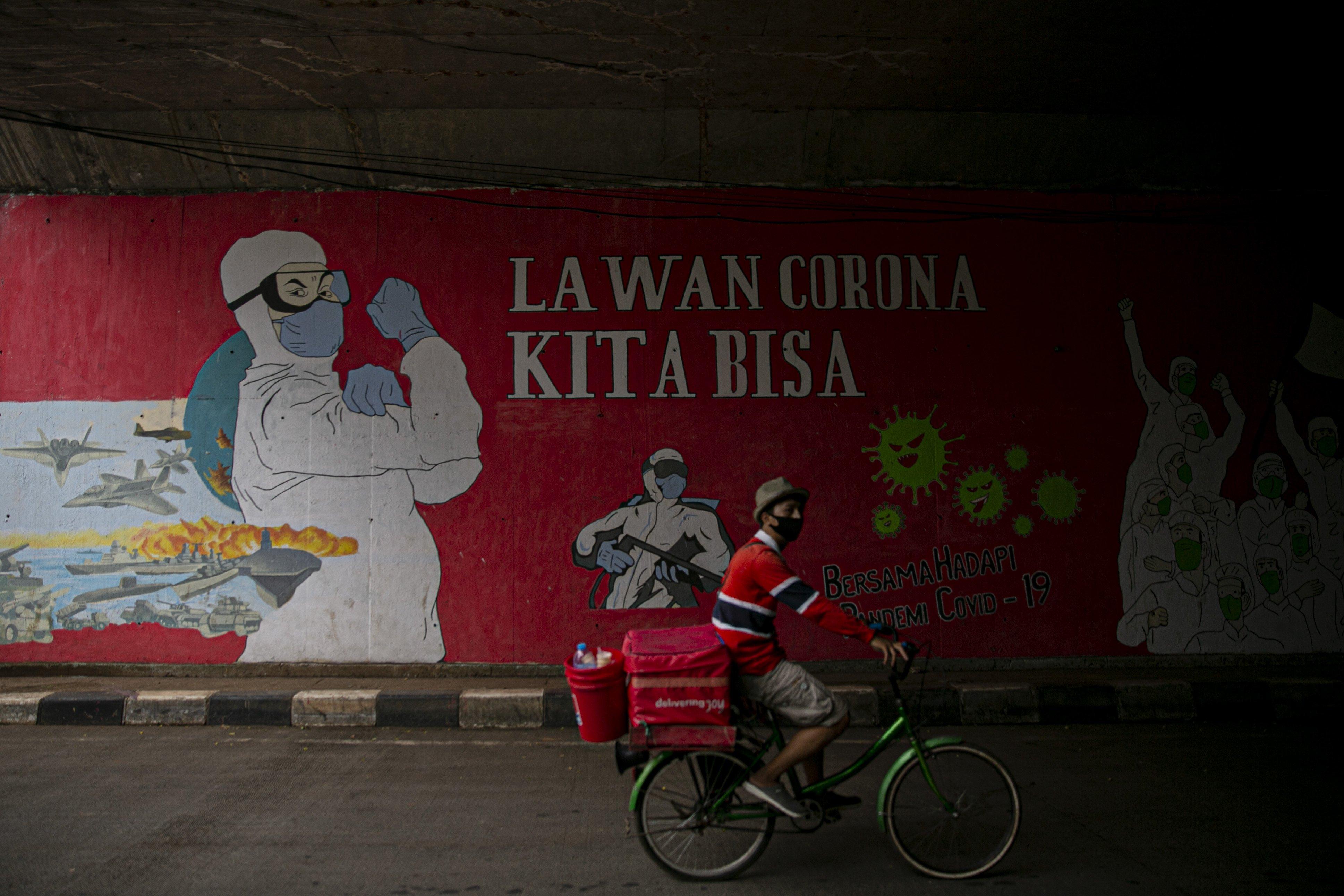Pengendara motor melintas di depan mural tentang pandemi COVID-19 di kawasan Pancoran, Jakarta, Senin (19/10/2020). Indonesia menempati peringkat pertama kasus terbanyak dan angka kematian akibat COVID-19 di Asia Tenggara dengan total 361.867 kasus konfirmasi dan meninggal sebanyak 12.511.