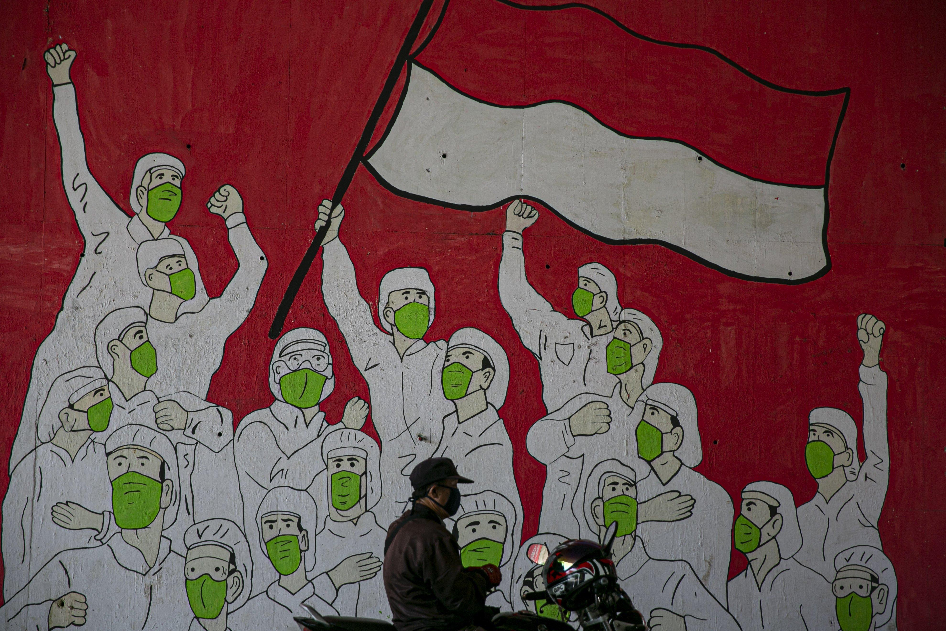 Pengendara motor melintas di depan mural tentang pandemi COVID-19 di kawasan Pancoran, Jakarta, Senin (19/10/2020).