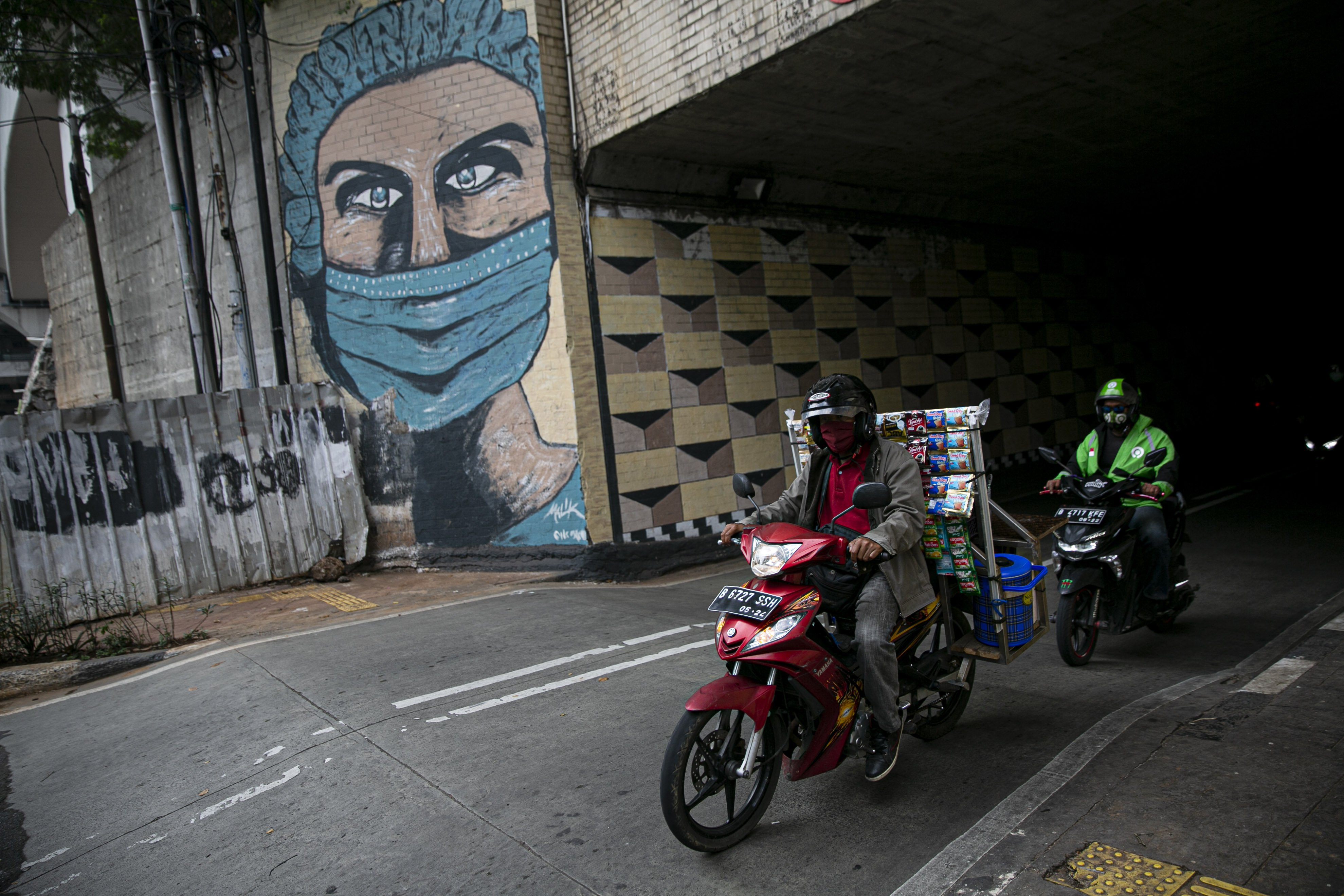 Pengendara melintas di depan mural tentang pandemi COVID-19 di kawasan Cipayung, Jakarta, Senin (19/10/2020). Indonesia menempati peringkat pertama kasus terbanyak dan angka kematian akibat COVID-19 di Asia Tenggara dengan total 361.867 kasus konfirmasi dan meninggal sebanyak 12.511.