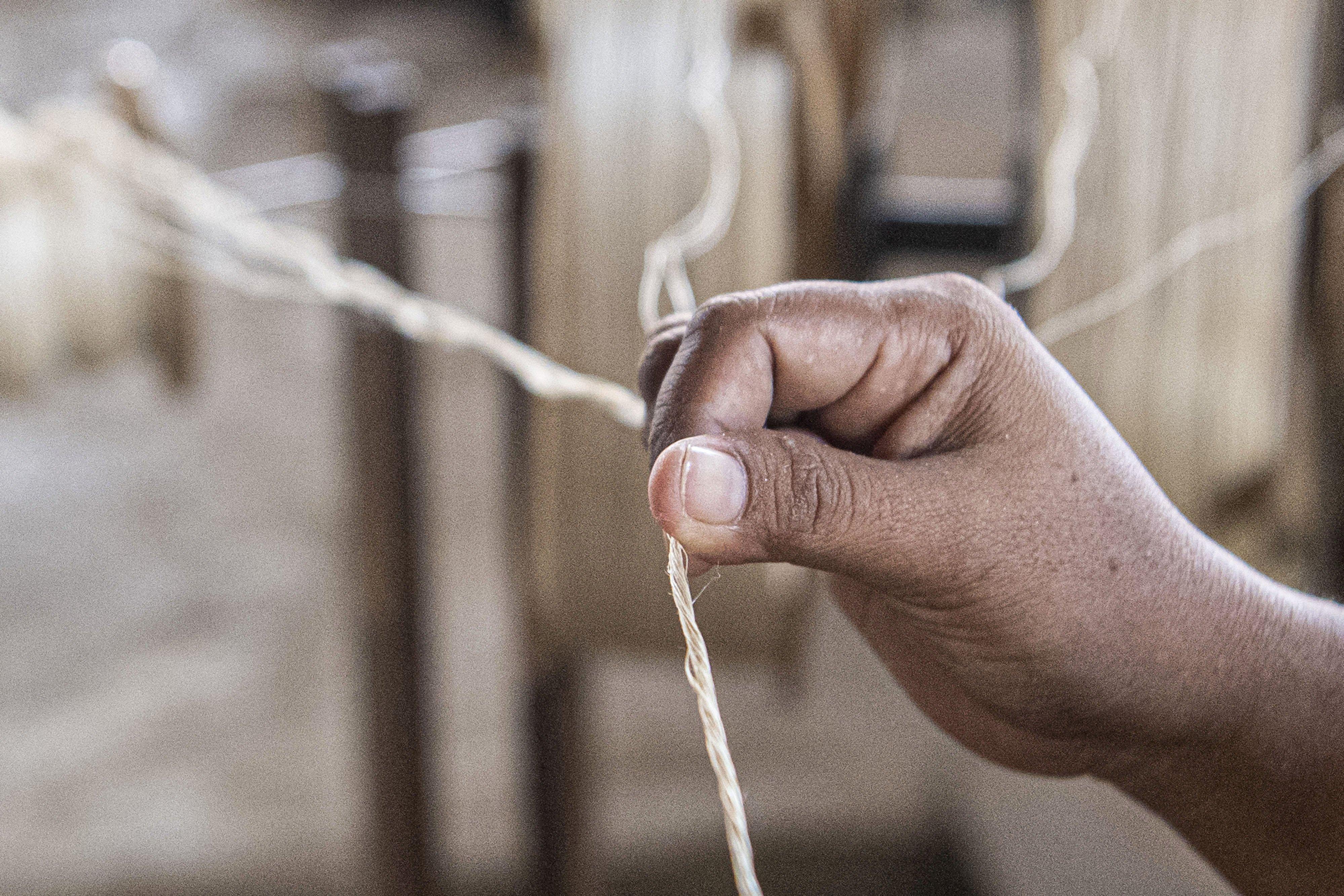 Pekerja memintal serat pohon pisang (abaca fiber) menjadi benang di bengkel anyam Djunaedi.