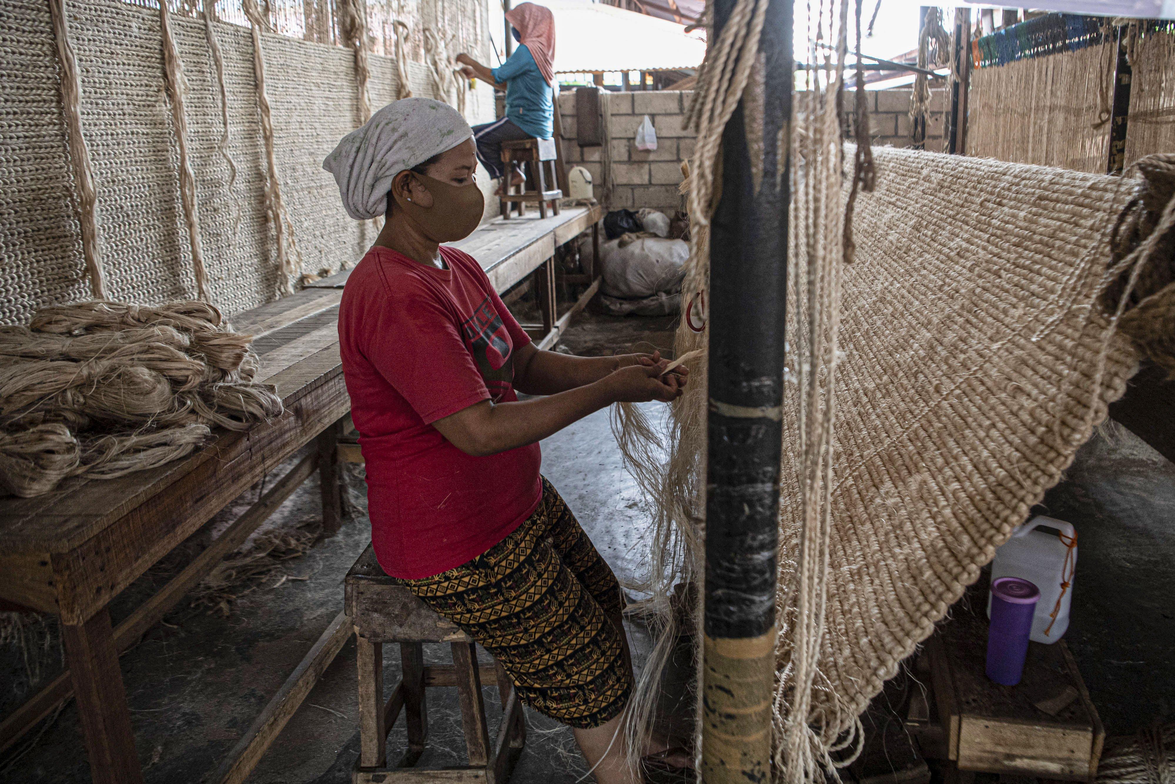 Sejumlah pekerja menganyam pintalan benang dari serat pohon pisang (abaca fiber) untuk dijadikan karpet di bengkel anyam Djunaedi.