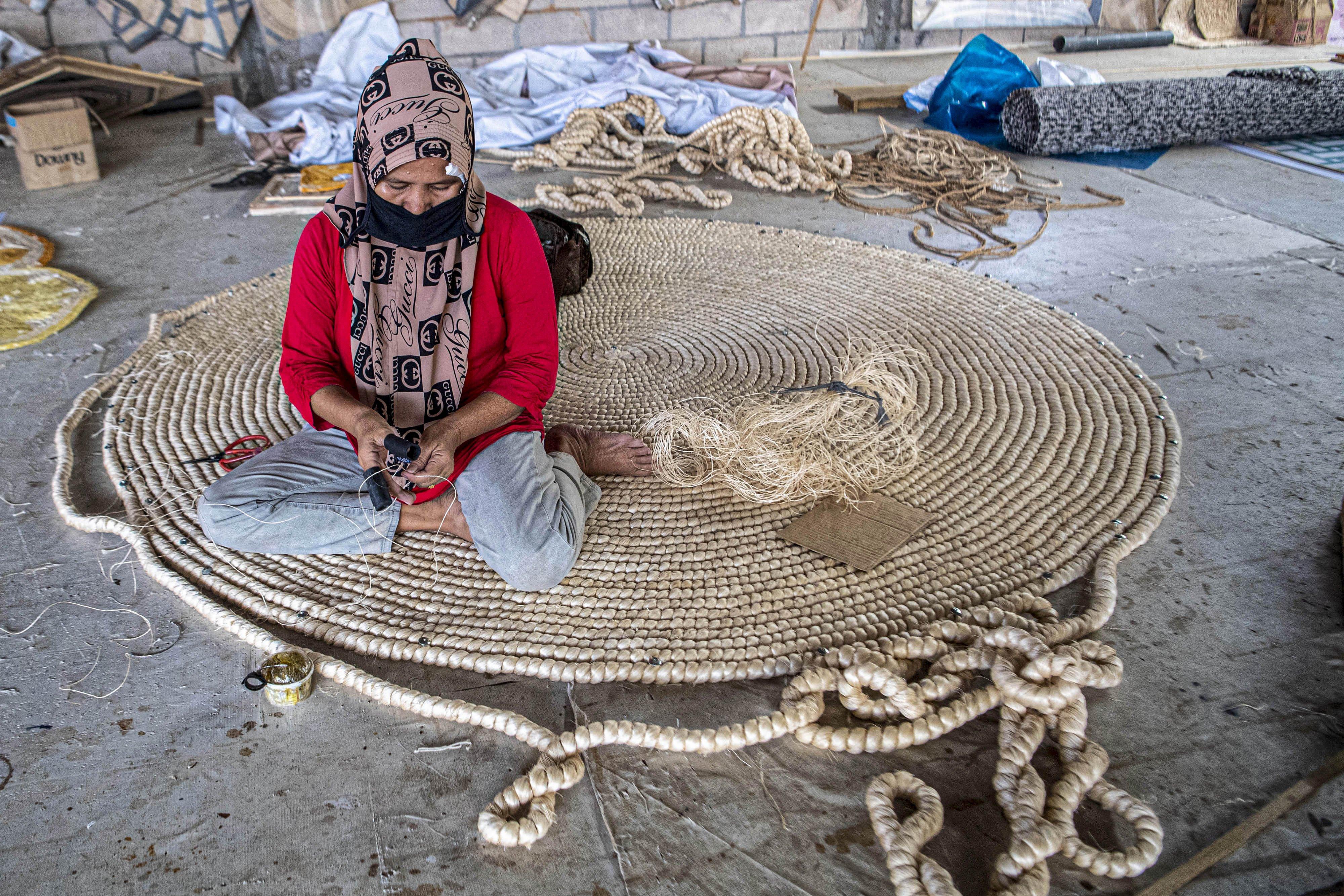 Pekerja menganyam karpet yang terbuat dari serat pohon pisang (abaca fiber) di bengkel anyam Djunaedi.\r\n