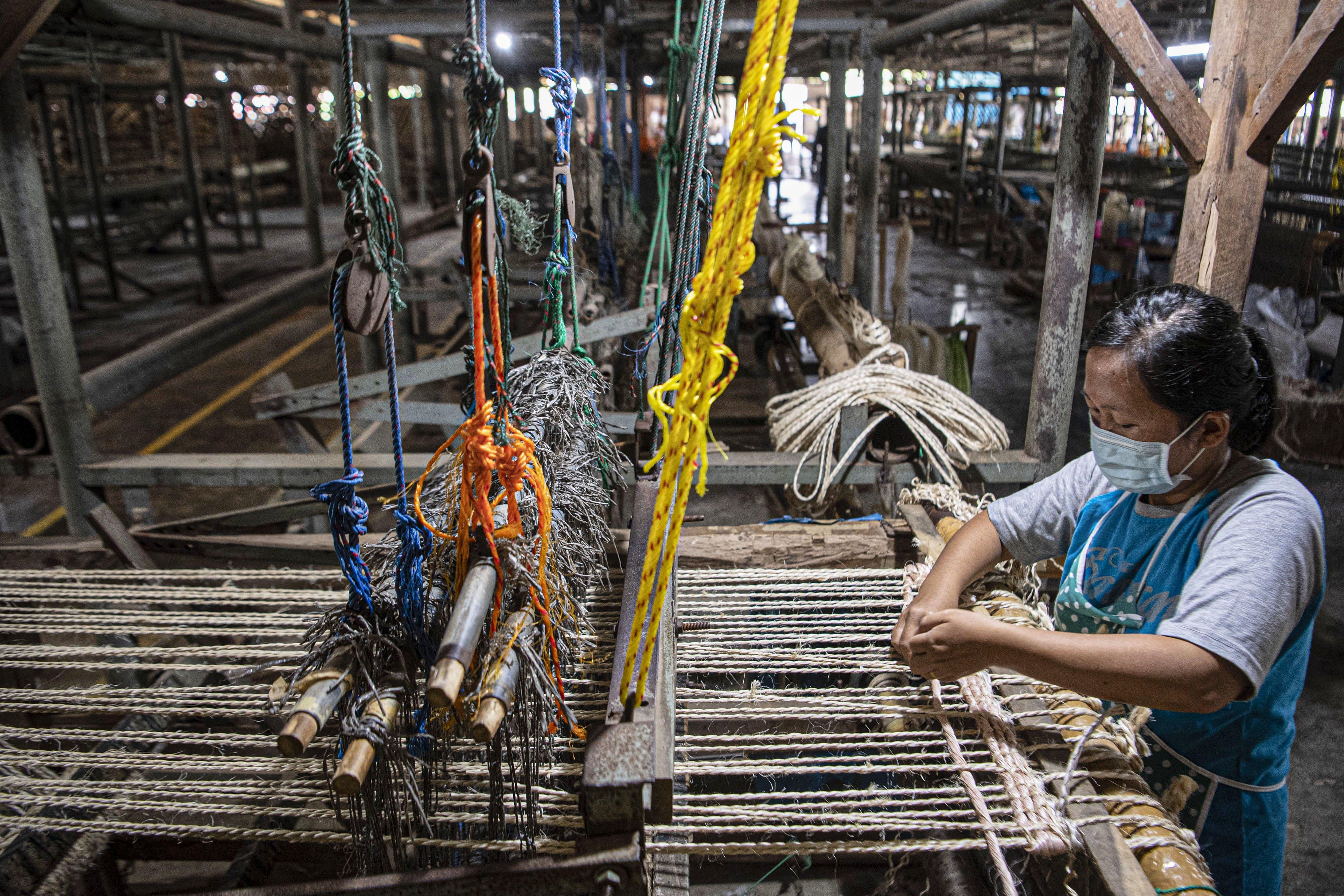 Sejumlah pekerja menganyam pintalan benang dari serat pohon pisang (abaca fiber) untuk dijadikan karpet di bengkel anyam Djunaedi.\r\n