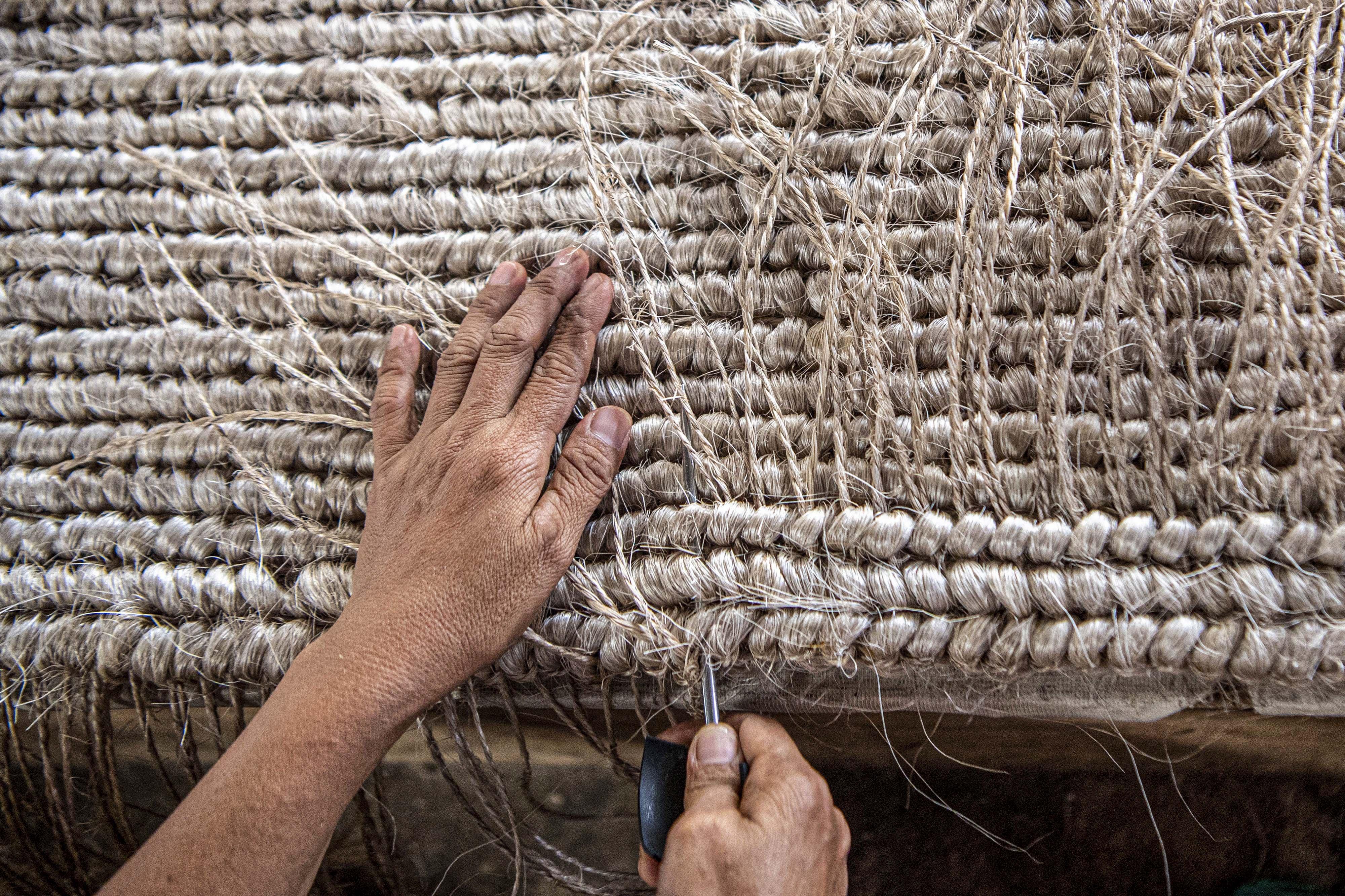 Pekerja menganyam pintalan benang dari serat pohon pisang (abaca fiber) untuk dijadikan karpet di bengkel anyam Djunaedi.