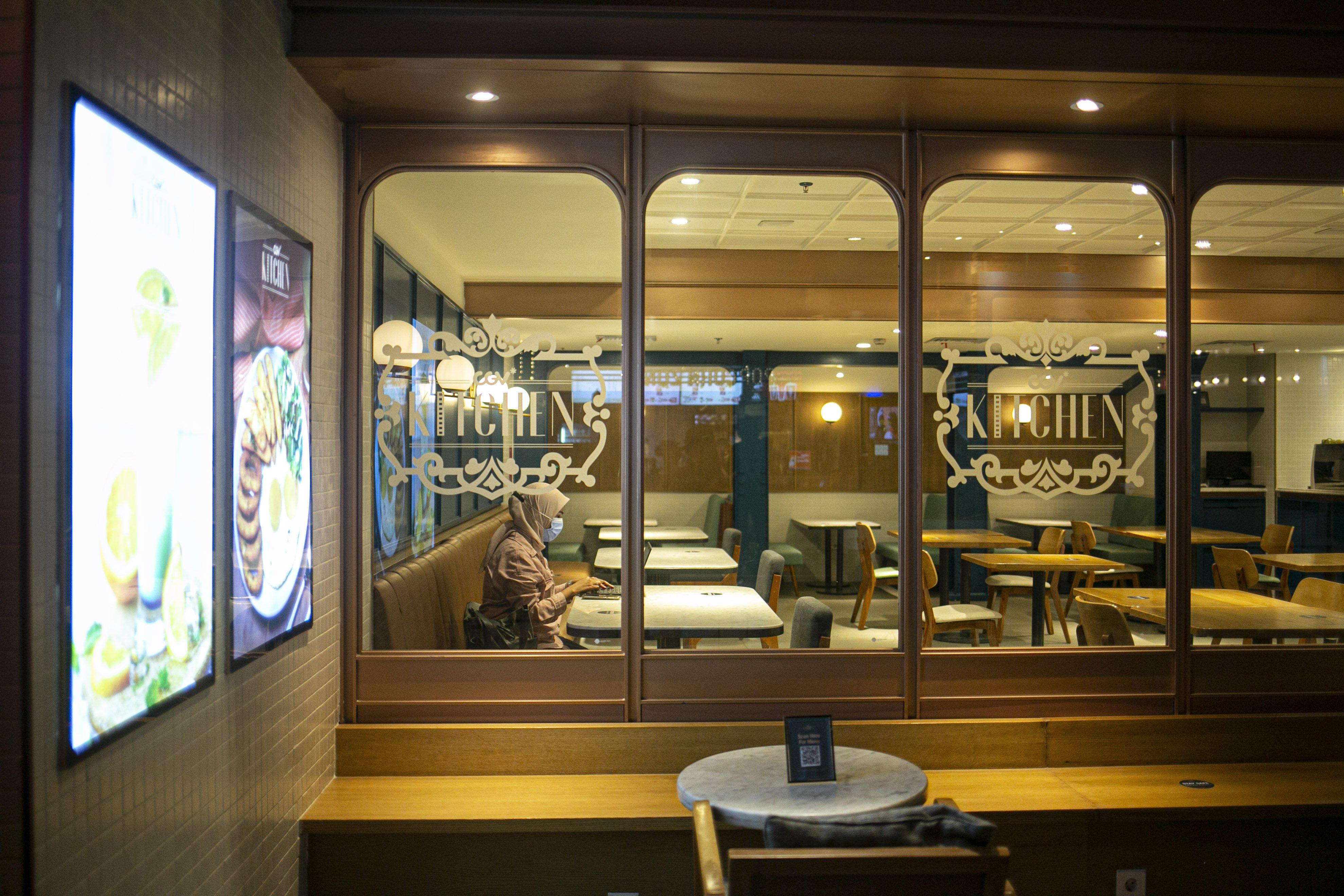 Pengunjung beraktivitas di restoran kawasan bioskop CGV Grand Indonesia Jakarta Pusat. PSBB Jawa Bali membatasi kapasitas dan jam operasional restoran.