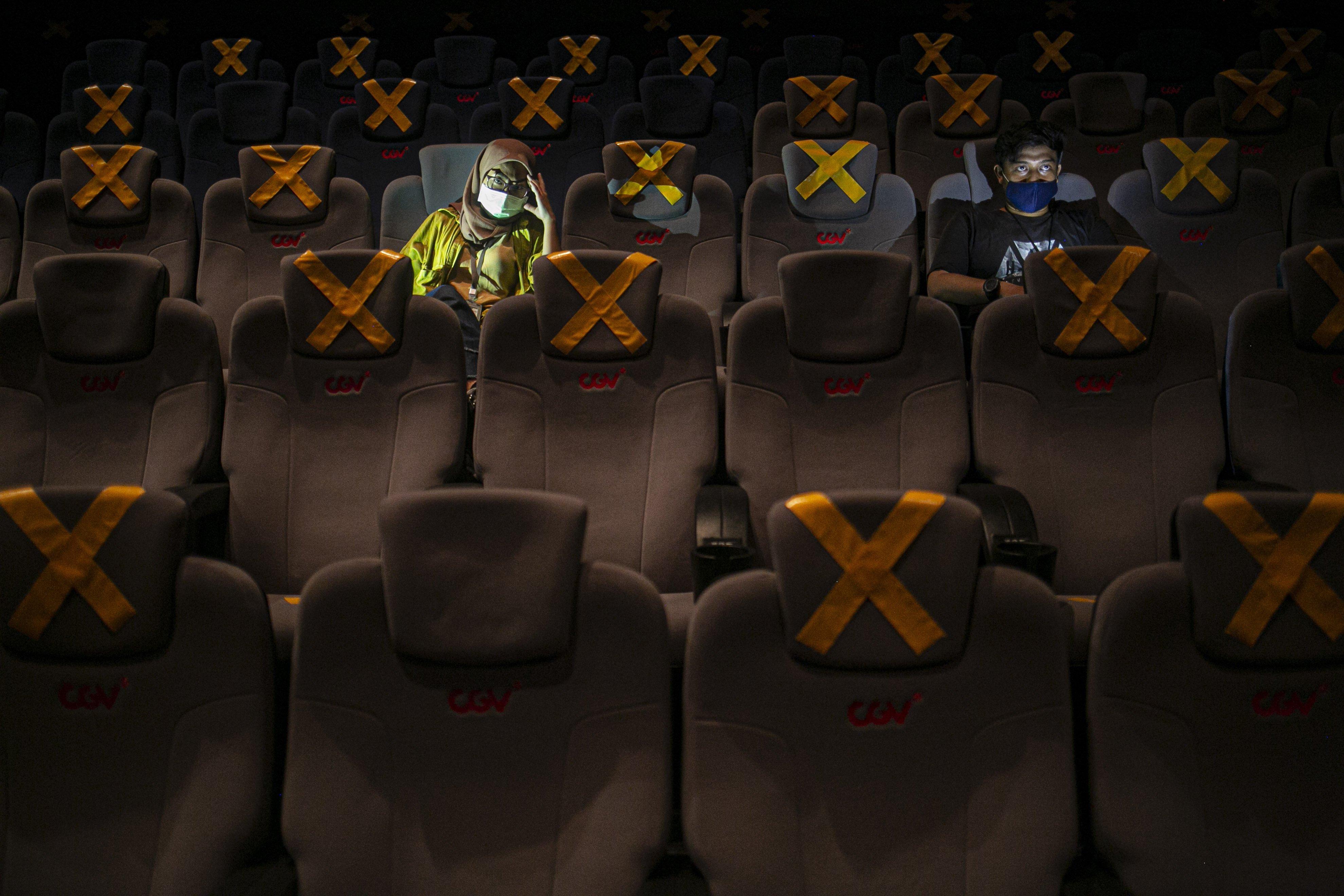 Petugas memasang tanda jaga jarak di bioskop CGV Grand Indonesia Jakarta Pusat, Rabu, (21/10/2020). Sejumlah bioskop di Ibu Kota kembali beroperasi per hari Rabu (21/10/2020) setelah mendapatkan izin dari Pemprov DKI Jakarta dengan jumlah penonton dibatasi maksimal 25 persen dari total kapasitas. Pihak bioskop menerapkan protokol kesehatan yang ketat dan tidak memperkenankan pengunjung untuk makan di dalam ruang bioskop.