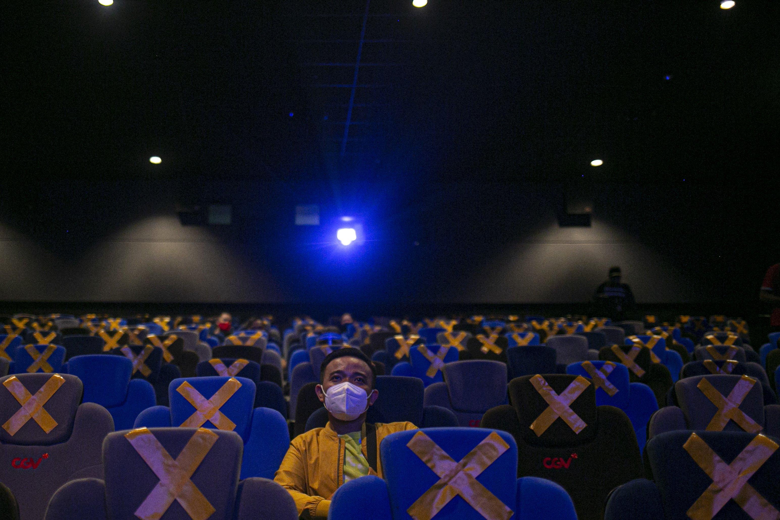 Pengunjung menonton film di bioskop CGV Grand Indonesia Jakarta Pusat, Rabu, (21/10/2020). Sejumlah bioskop di Ibu Kota kembali beroperasi per hari Rabu (21/10/2020) setelah mendapatkan izin dari Pemprov DKI Jakarta dengan jumlah penonton dibatasi maksimal 25 persen dari total kapasitas. Pihak bioskop menerapkan protokol kesehatan yang ketat dan tidak memperkenankan pengunjung untuk makan di dalam ruang bioskop.