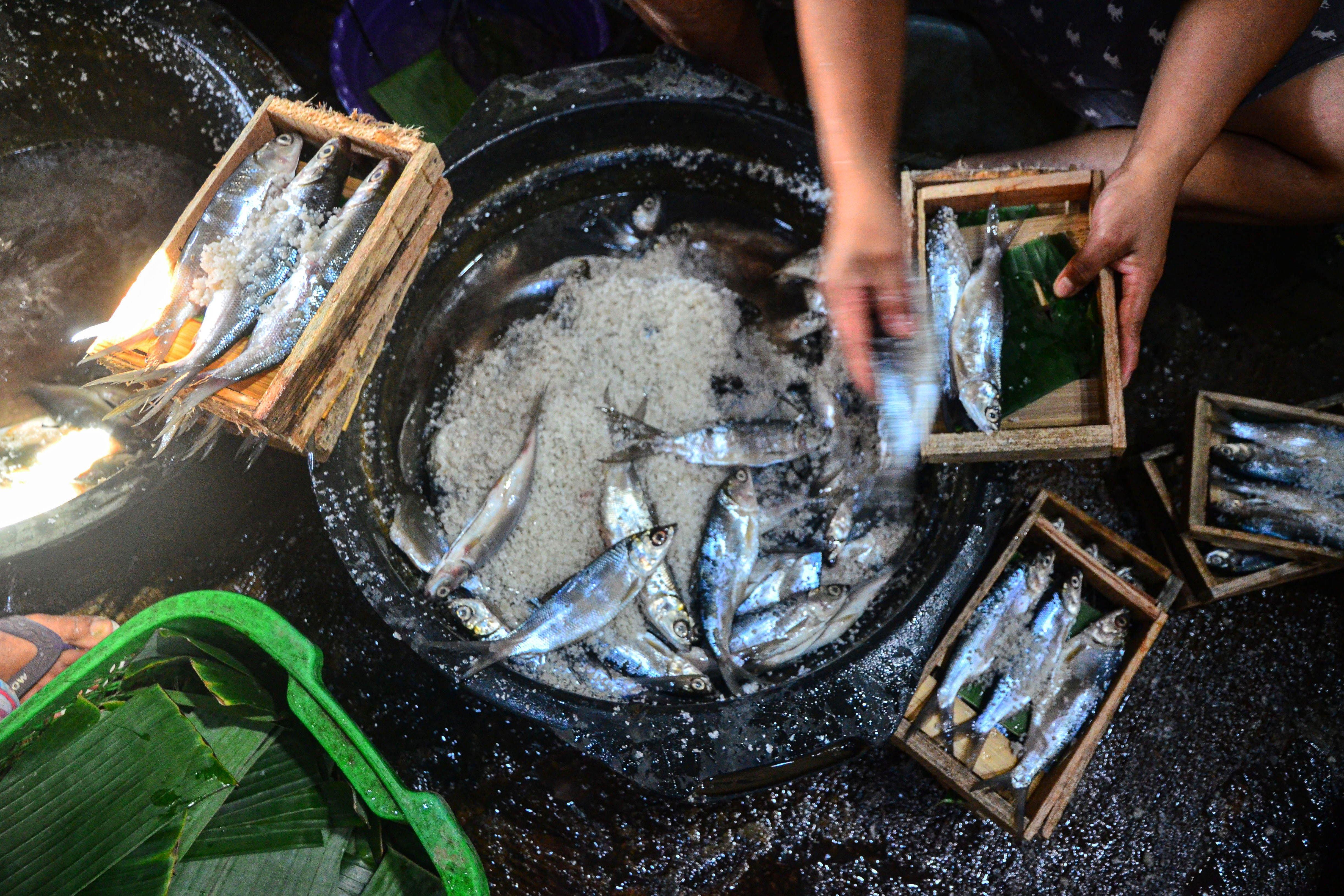 Pekerja menaburi bumbu garam pada ikan bandeng di Desa Dukutalit, Juwana, Pati, Jawa Tengah.\r\n