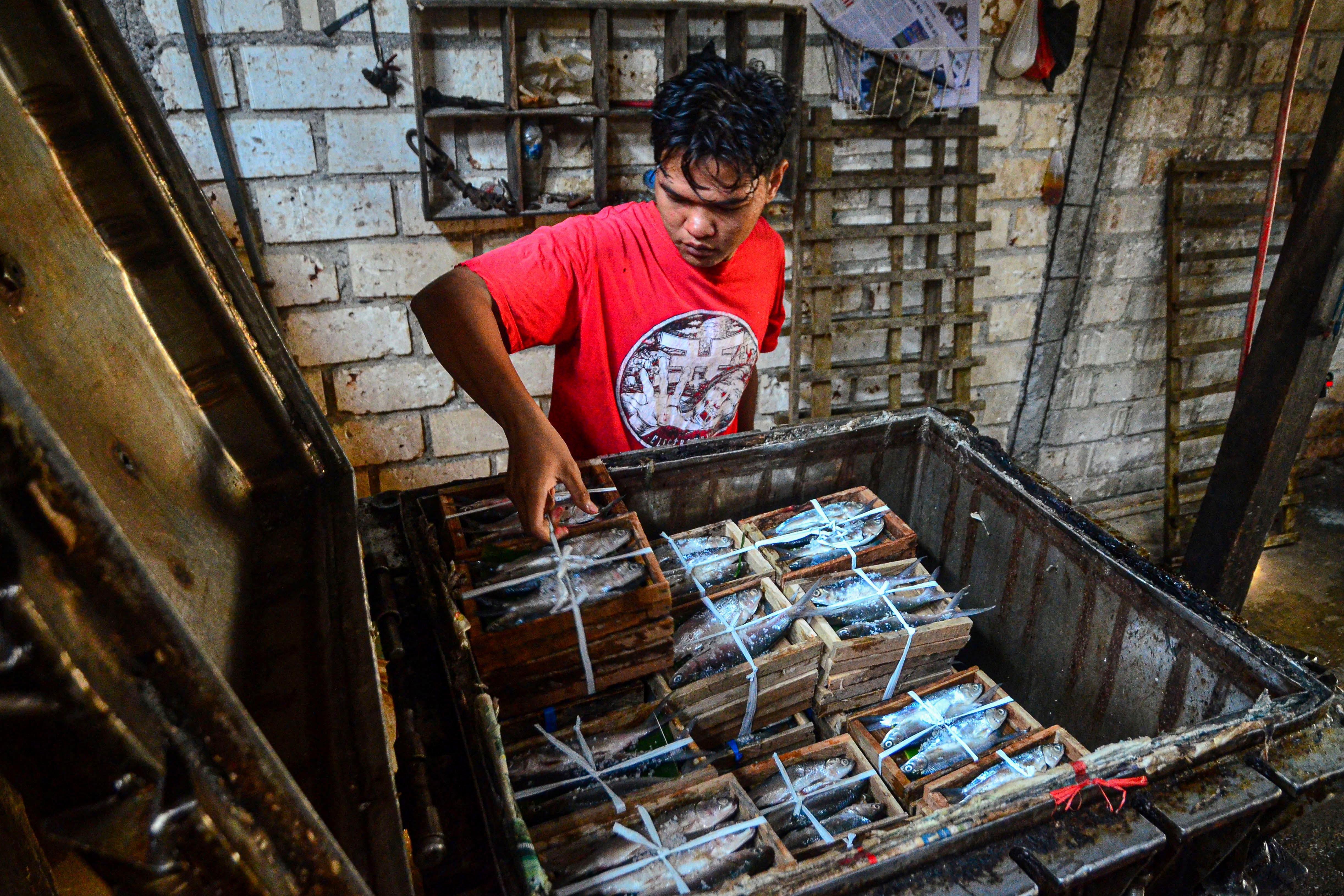Pekerja memasukkan ikan bandeng ke dalam panci presto di Desa Dukutalit, Juwana, Pati, Jawa Tengah.\r\n