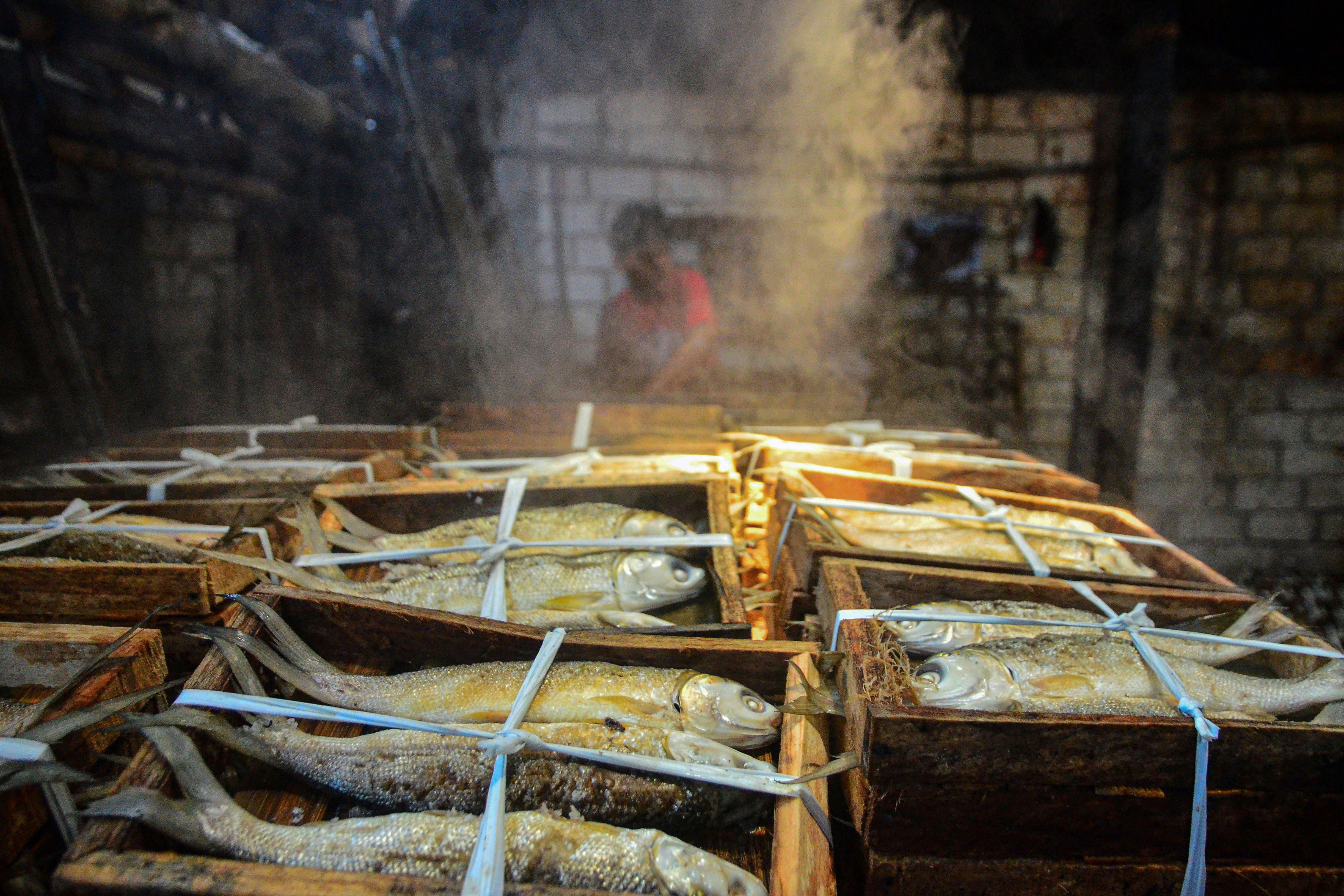 Pekerja memasukkan ikan bandeng ke dalam panci presto di Desa Dukutalit, Juwana, Pati, Jawa Tengah.