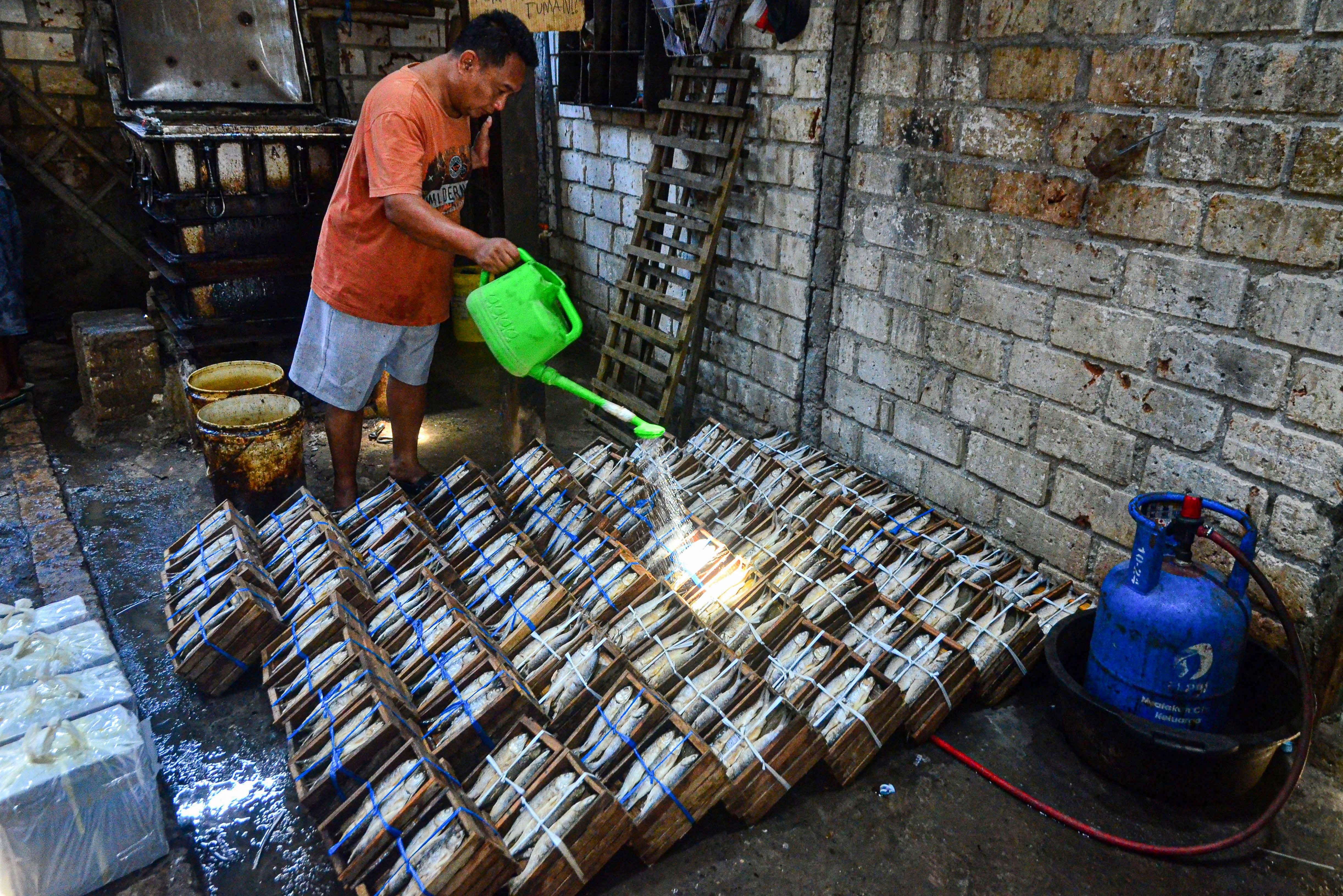 Pemilik usaha pengolahan ikan membesihkan bandeng presto di Desa Dukutalit, Juwana, Pati, Jawa Tengah.\r\n