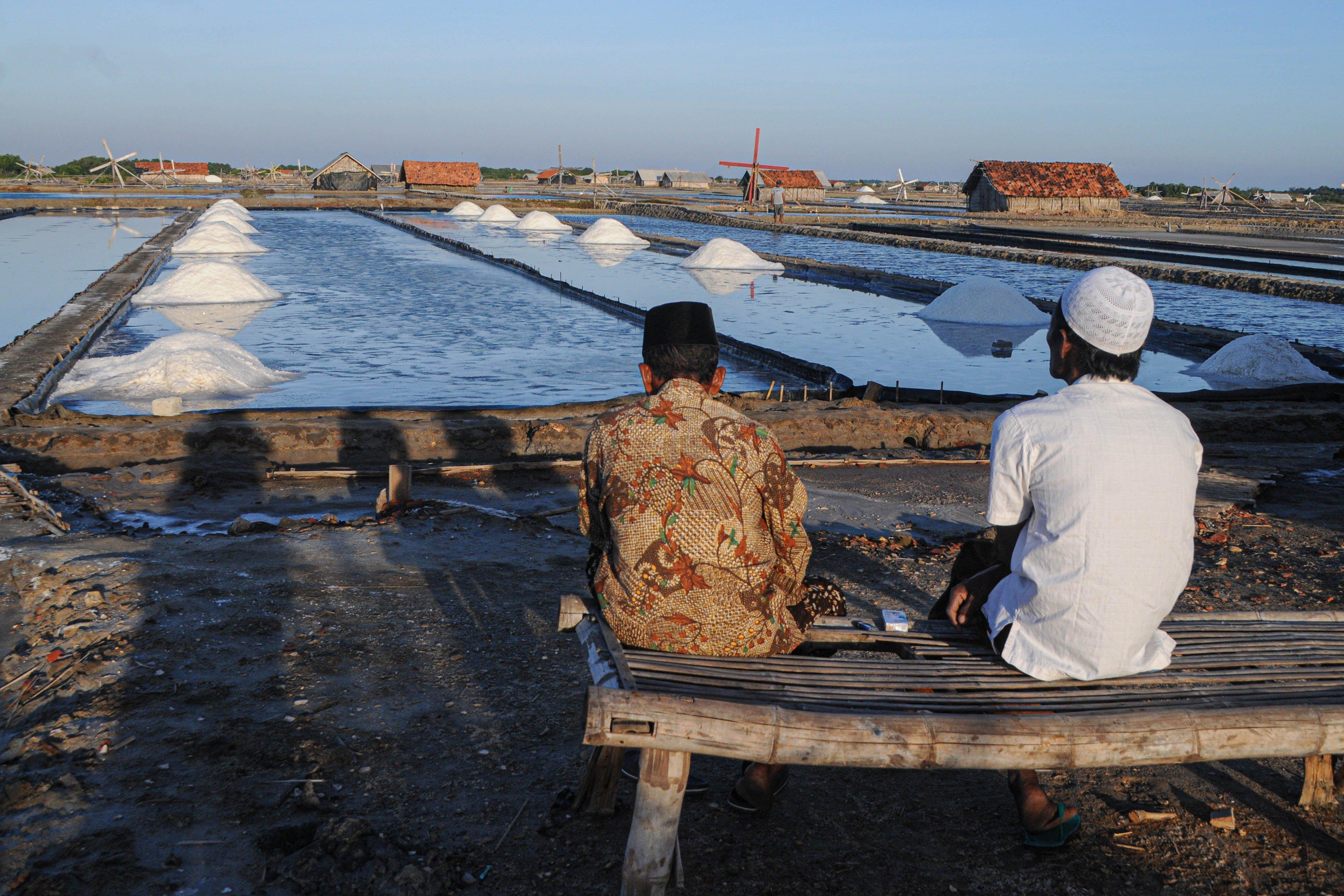 Petani berbincang sambil memandangi tumpukan garam yang baru dipanen di Desa Bunder, Pamekasan, Jawa Timur.