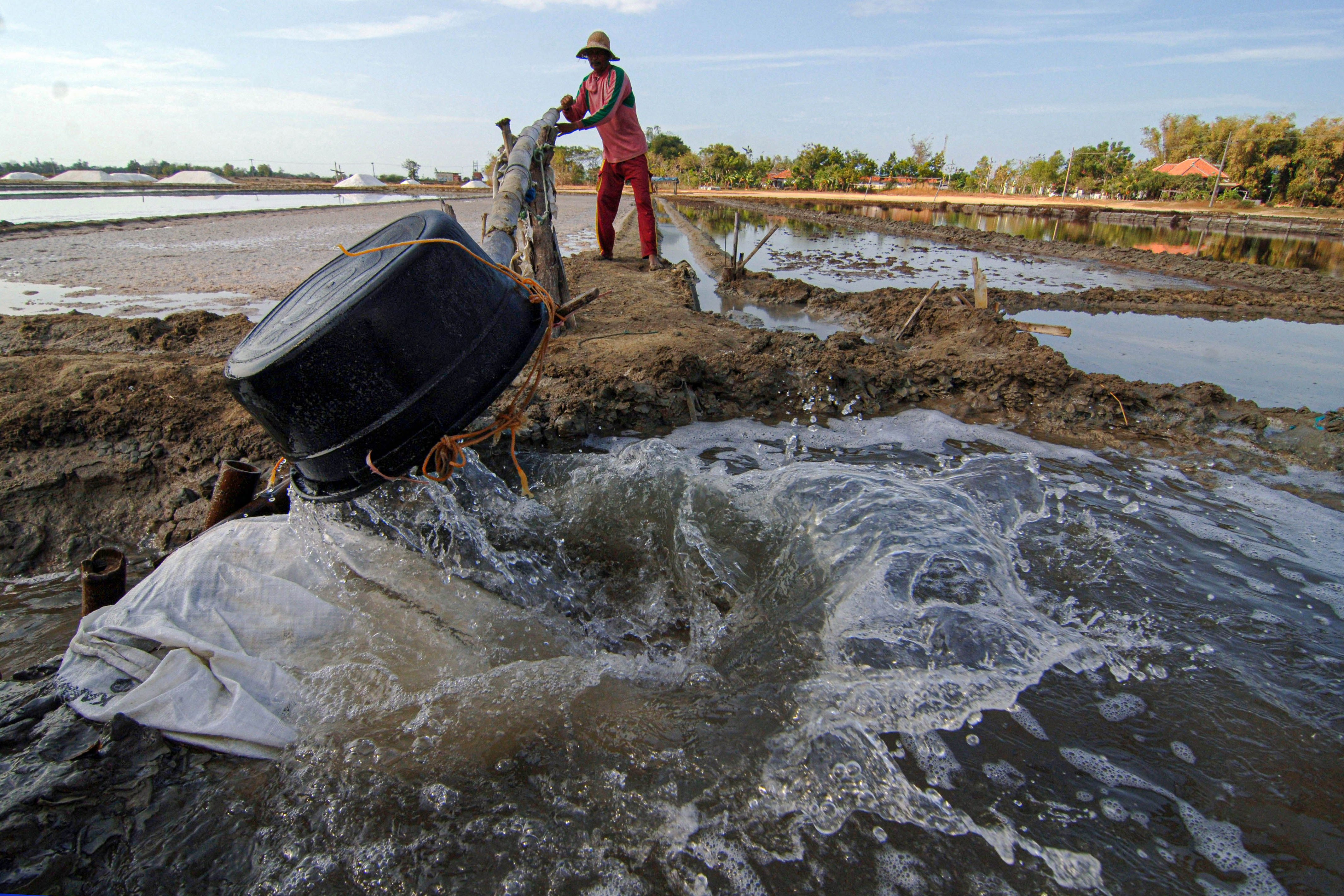 Petani memasukkan air laut ke dalam penampungan sementara secara manual ketika hembusan angin tidak mampu menggerakkan baling-baling di Desa Bunder, Pademawu, Pamekasan, Jawa Timur.