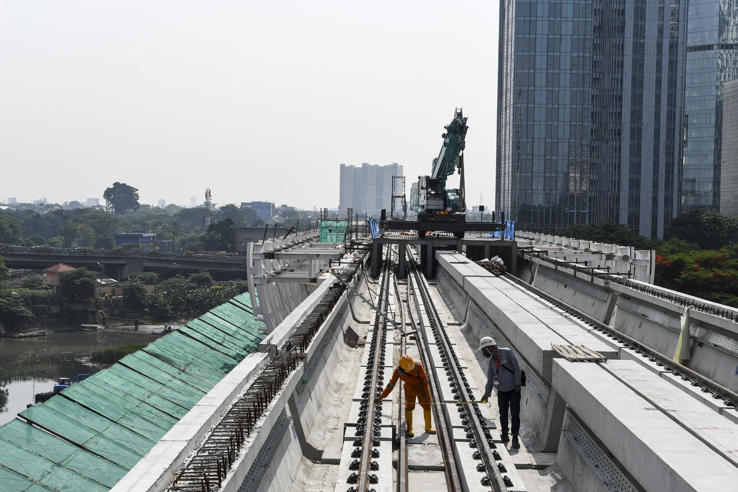 Dua orang pekerja menyelesaikan proyek pembangunan 'longspan' atau jembatan bentang panjang lintasan 'Light Rail Transit (LRT)' di kawasan Dukuh Atas, Jakarta, Rabu (11/11/2020). PT Adhi Karya (Persero) Tbk telah menyelesaikan pembangunan longspan terakhir sepanjang 218 meter yang menghubungkan lintasan LRT dari Cawang-Kuningan-Dukuh Atas.