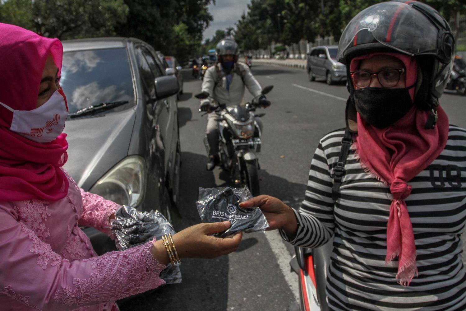 Pegawai dari Dinas Kesehatan Provinsi Riau bersama komunitas relawan membagikan masker kepada pengguna jalan raya di Jalan Sudirman, Pekanbaru, Riau, Kamis (12/11/2020). Dalam memperingati Hari Kesehatan Nasional yang ke-56 Dinas Kesehatan Provinsi Riau membagikan sebanyak tujuh ribu masker untuk masyarakat sekaligus mengingatkan kembali untuk tetap mematuhi protokol kesehatan COVID-19.