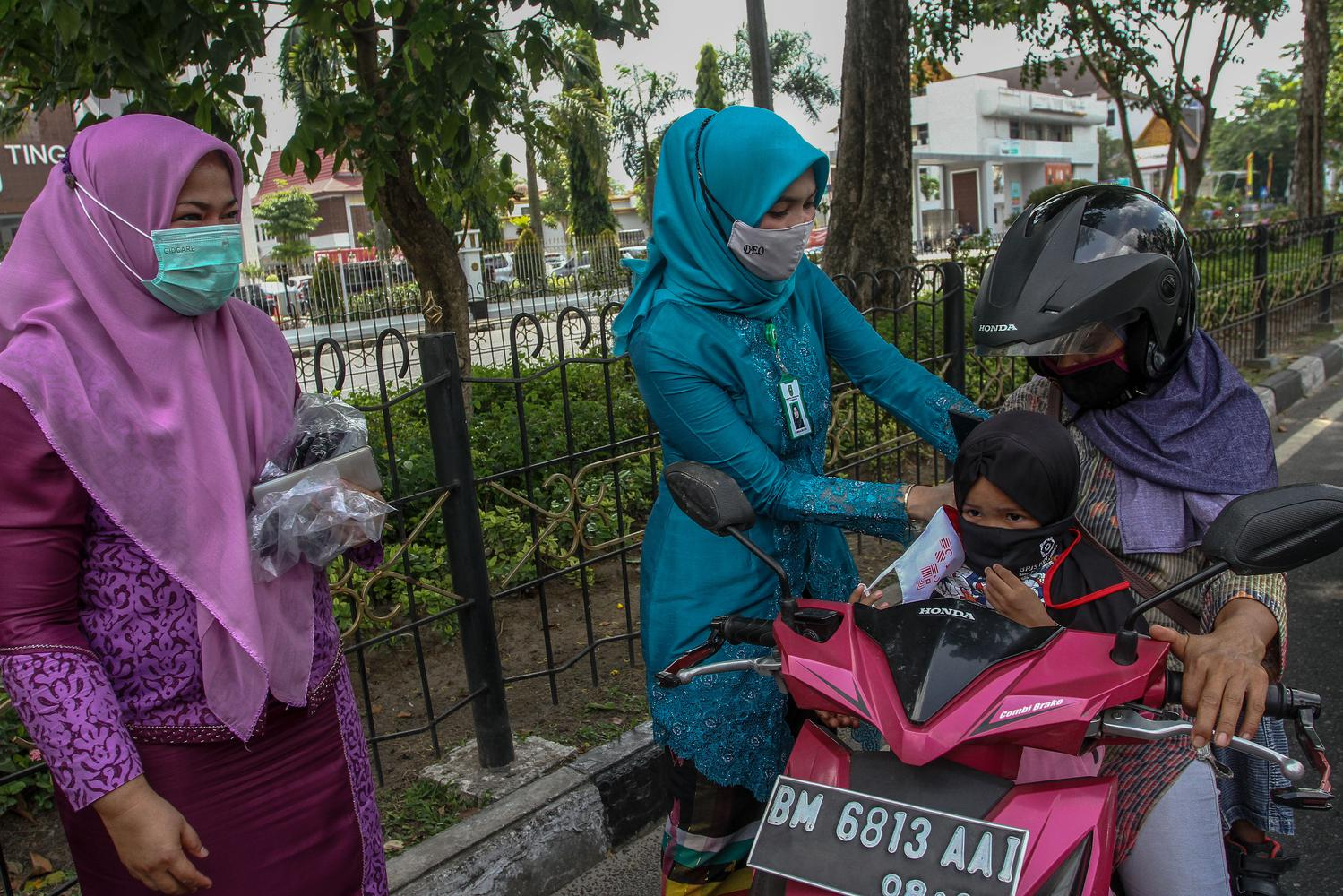 Pegawai dari Dinas Kesehatan Provinsi Riau bersama komunitas relawan membantu memasangkan masker kepada pengguna jalan raya di Jalan Sudirman, Pekanbaru, Riau, Kamis (12/11/2020). Dalam memperingati Hari Kesehatan Nasional yang ke-56 Dinas Kesehatan Provinsi Riau membagikan sebanyak tujuh ribu masker untuk masyarakat sekaligus mengingatkan kembali untuk tetap mematuhi protokol kesehatan COVID-19.