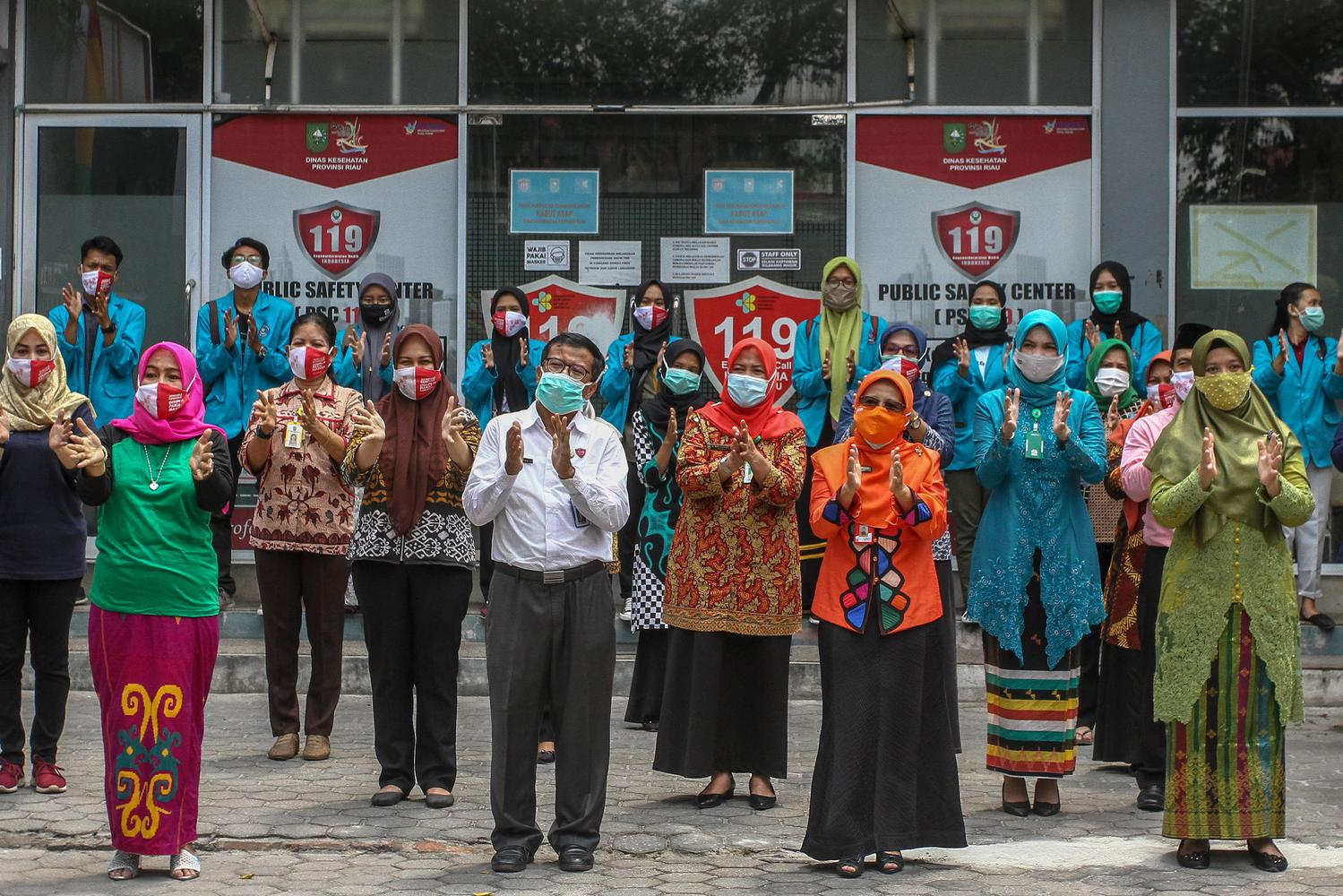 Pegawai Dinas Kesehatan Provinsi Riau bersama komunitas relawan peduli kesehatan bertepuk tangan selama 56 detik di halaman Kantor Dinkes Provinsi Riau di Pekanbaru, Riau, Kamis (12/11/2020). Selain untuk memperingati Hari Kesehatan Nasional ke-56, kegiatan tersebut juga sebagai bentuk apresiasi serta dukungan terhadap para seluruh petugas yang berjuang melawan COVID-19 dan juga kepada masyarakat yang telah melaksanakan protokol kesehatan.