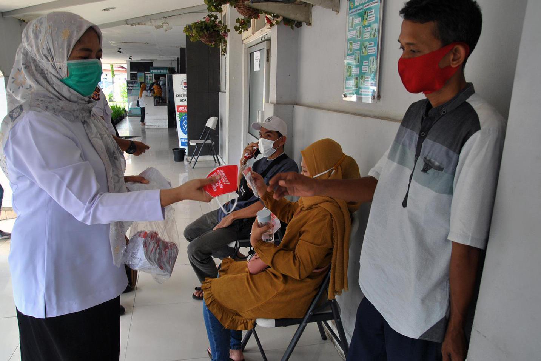 Petugas kesehatan membagikan masker kepada warga di RSUD Kota Bogor, Jawa Barat, Kamis (12/11/2020). Kegiatan tepuk tangan bersama dan pembagian masker berbahan kain tersebut selain dalam rangka memperingati Hari Kesehatan Nasional ke-56 sekaligus sebagai apresiasi terhadap perjuangan tenaga kesehatan dalam pencegahan dan penanganan COVID-19 serta masyarakat yang telah patuh dalam melaksanakan protokol kesehatan.