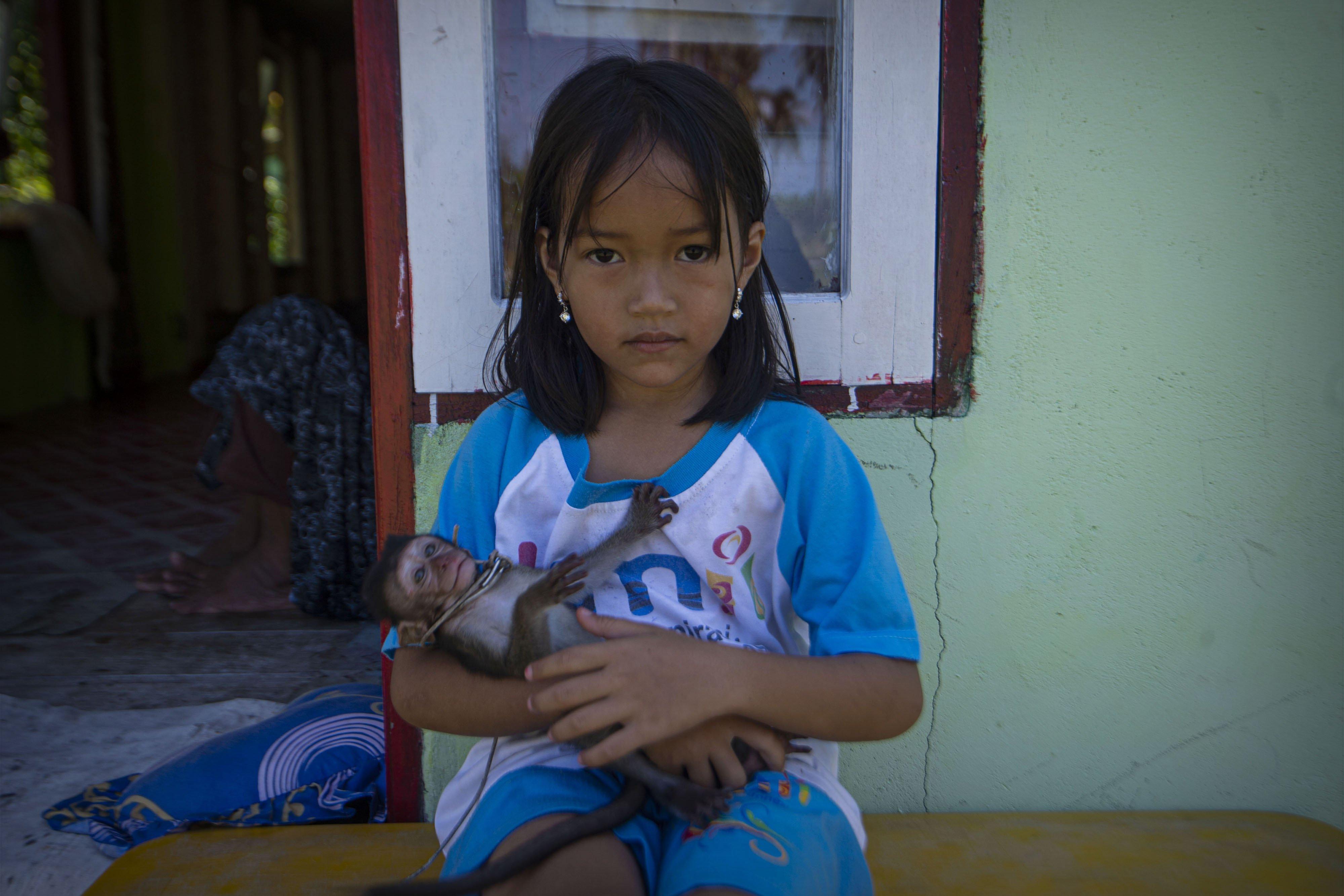 Seorang anak menggendong kera peliharaannya di depan rumahnya Desa Air Payang di Pulau Laut, Kabupaten Natuna, Kepulauan Riau.